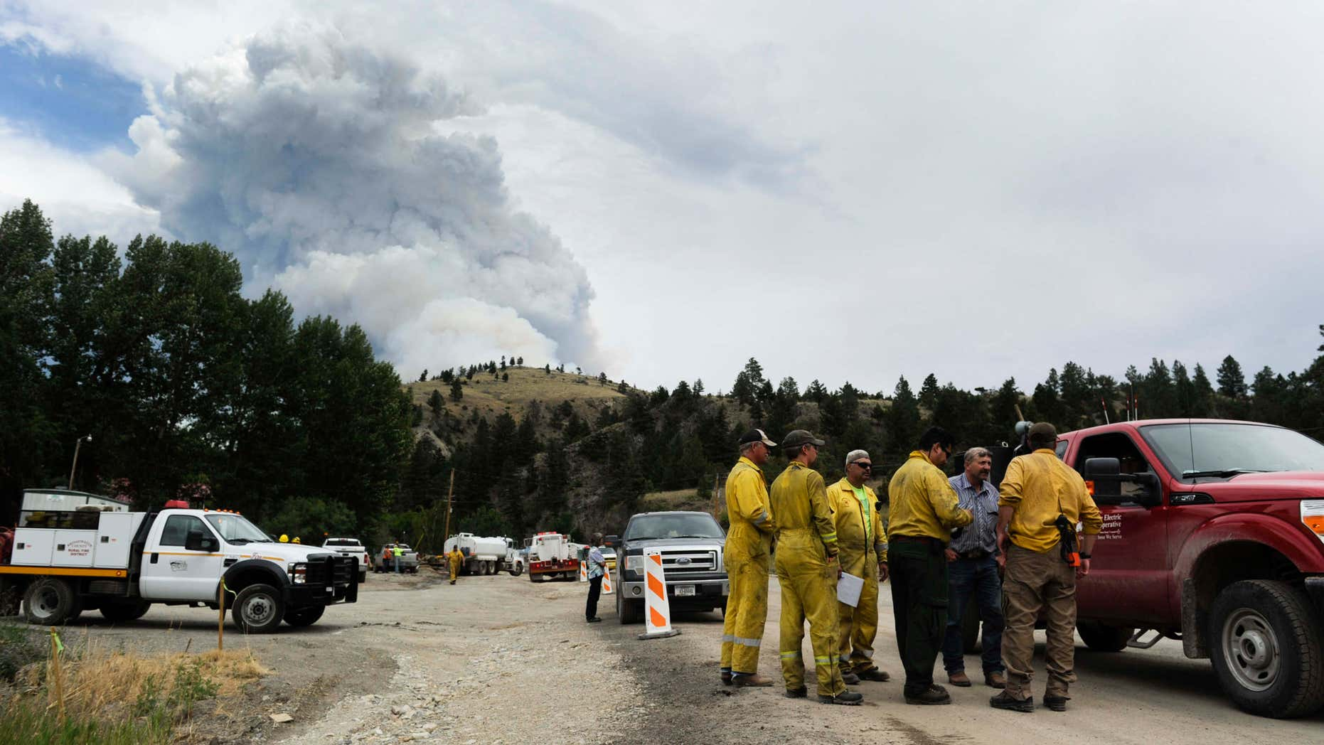 July 21, 2015: Wildland firefighters chat with Deep Creek landowners as smoke rises from a wildfire near Townsend, Mont.