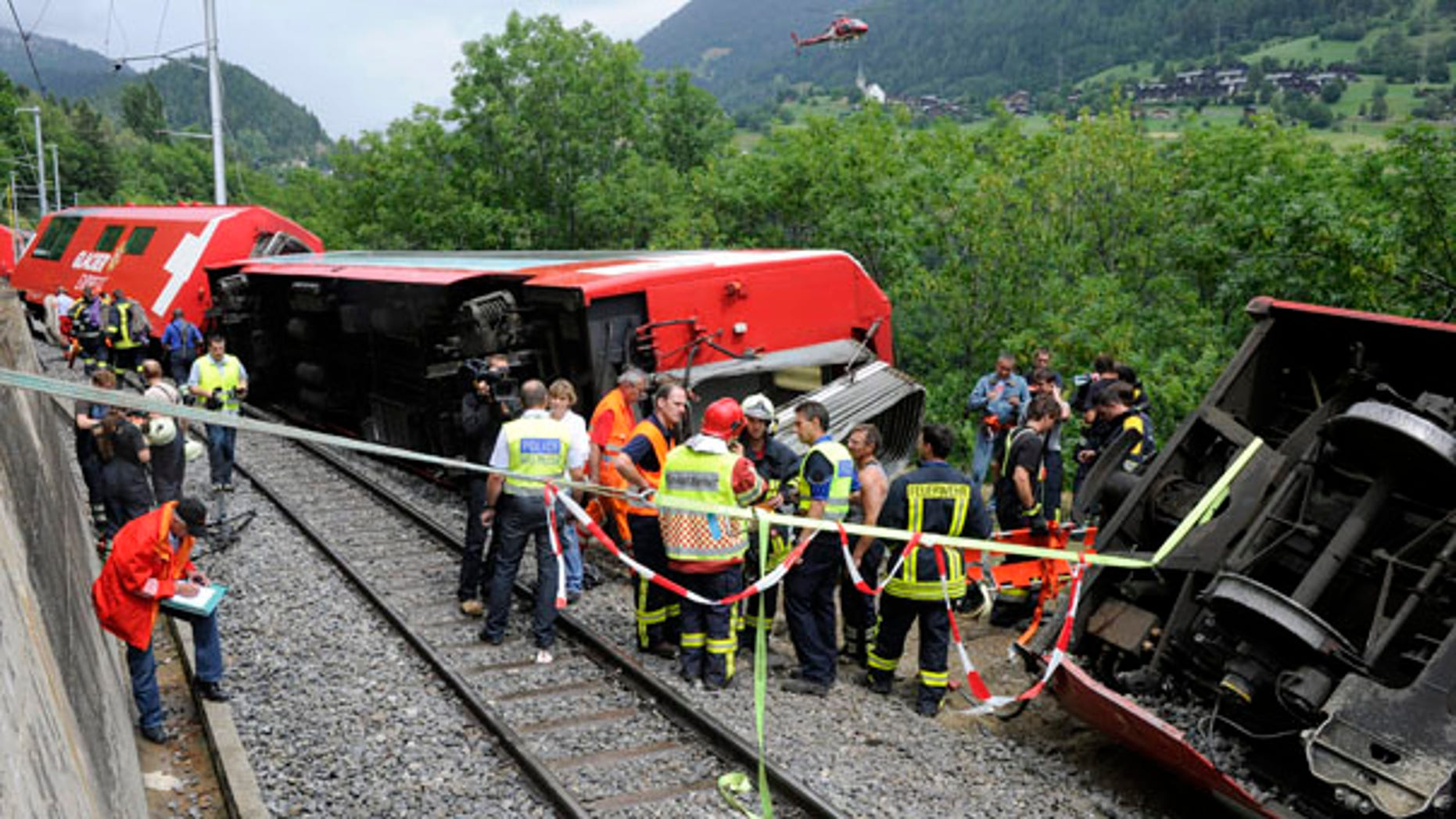 July 23: Rescue workers survey the damaged carriages of a Glacier Express passenger train after the trouist train derailed in Fiesch, Switzerland, killing one passenger and injuring more than 40.