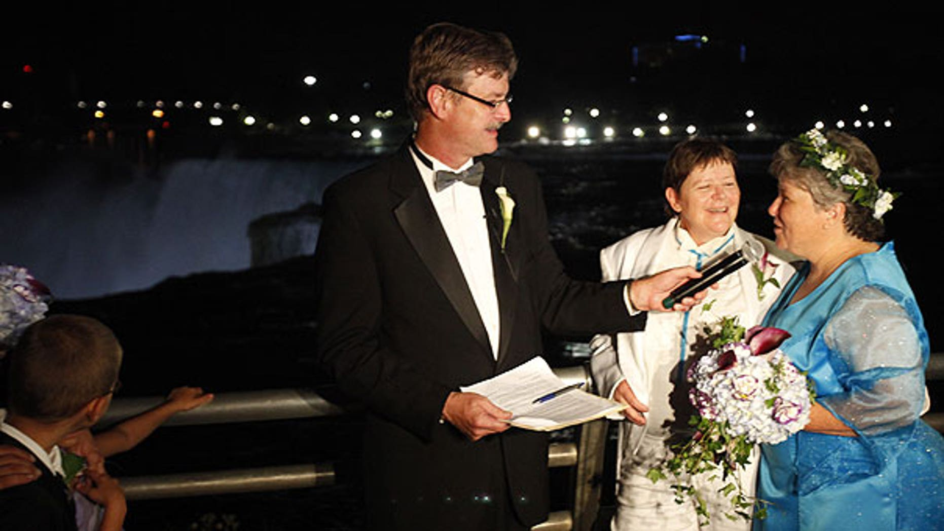 July 24: Kitty Lambert, right, and Cheryle Rudd are married by Niagara Falls Mayor Paul Dyster, left, in Niagara Falls, N.Y.