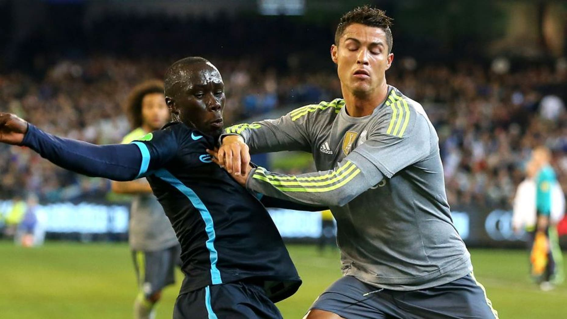 MELBOURNE, AUSTRALIA - JULY 24: Bacary Sagna of Manchester City and Cristiano Ronaldo of Real Madrid compete for the ball during the International Champions Cup match between Real Madrid and Manchester City at Melbourne Cricket Ground on July 24, 2015 in Melbourne, Australia. (Photo by Quinn Rooney/Getty Images)