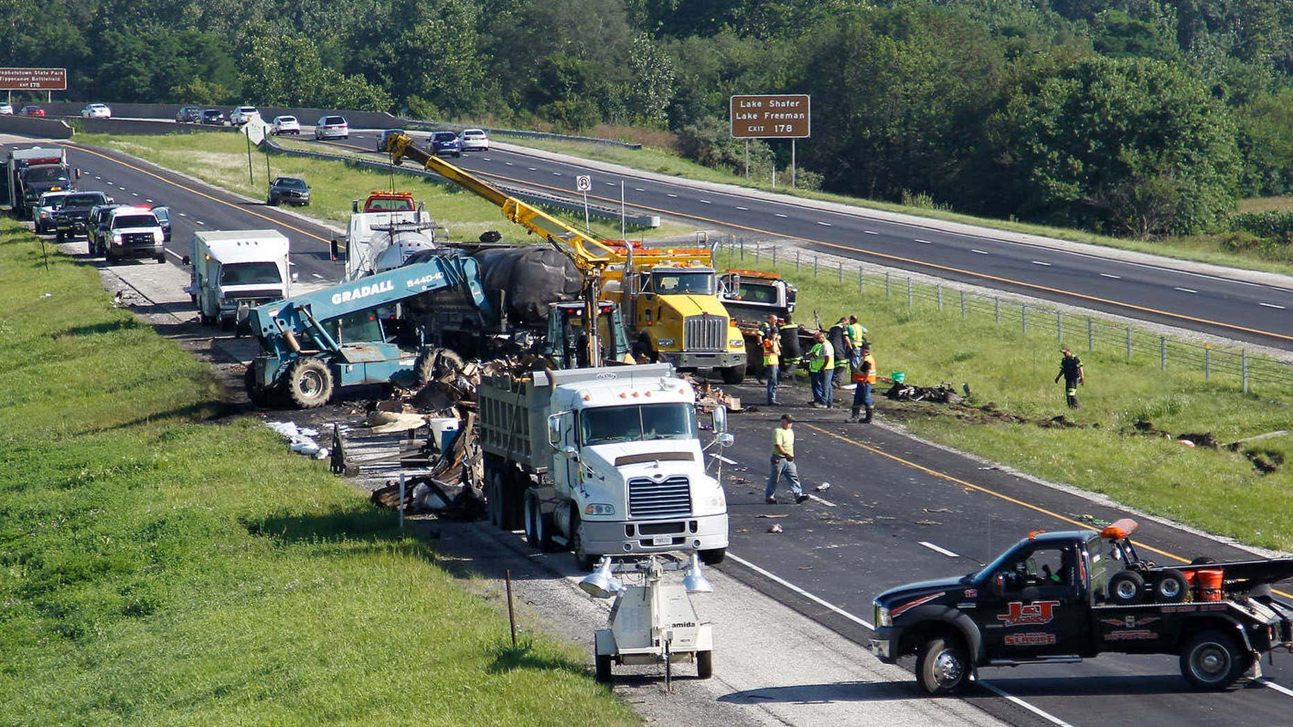 July 24, 2015: Crews cleanup debris following a fiery crash.