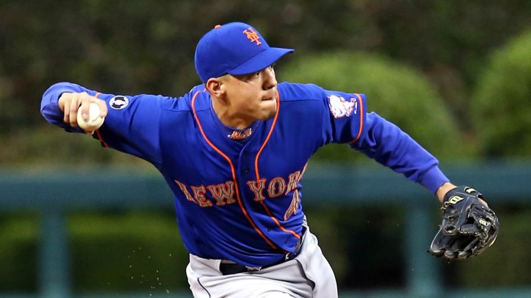 May 29, 2014; Philadelphia, PA, USA; New York Mets shortstop Wilmer Flores (4) attempts to throw out a runner in the second inning of a game against the Philadelphia Phillies at Citizens Bank Park. Mandatory Credit: Bill Streicher-USA TODAY Sports