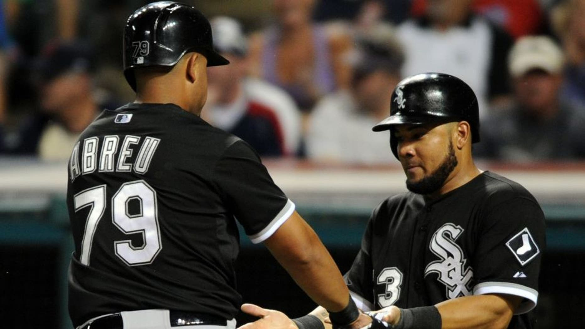 Jul 24, 2015; Cleveland, OH, USA; Chicago White Sox first baseman Jose Abreu (79) and Chicago White Sox left fielder Melky Cabrera (53) celebrate after scoring during the eighth inning against the Cleveland Indians at Progressive Field. The White Sox won 6-0.