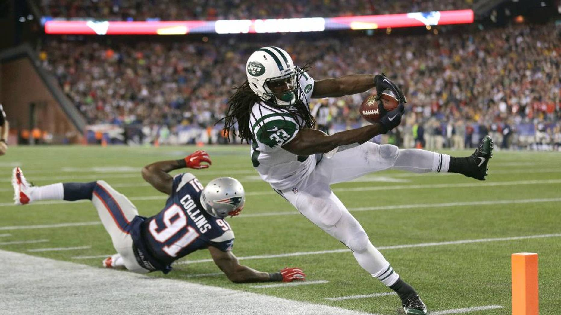 New York Jets running back Chris Ivory (33) goes out of bounds just short of the goal line next to New England Patriots outside linebacker Jamie Collins (91) in the second half of an NFL football game Thursday, Oct. 16, 2014, in Foxborough, Mass. (AP Photo/Charles Krupa)