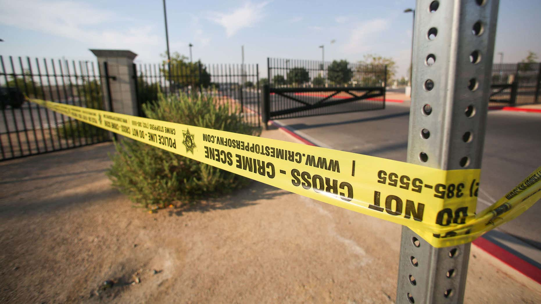 """Police tape hangs at Gary Reese Freedom Park, where police say a shooting erupted when a man in a vehicle attempted to rob a group of people playing """"Pokemon GO"""" early Monday, July 25, 2016, in Las Vegas."""