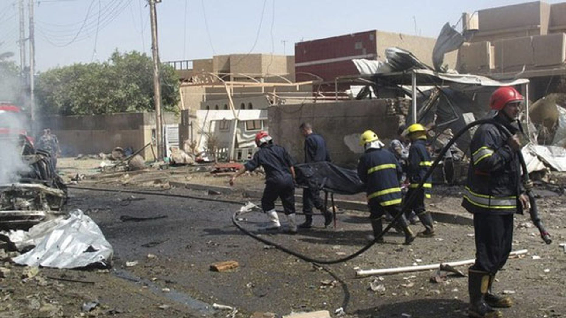 July 26: Rescue workers carry the body of a victim who was killed in a bomb attack in Baghdad. A homicide bomber killed at least four people on Monday in the attack that appeared to target the office of Dubai-based Al-Arabiya television in Baghdad, security officials said (Reuters).