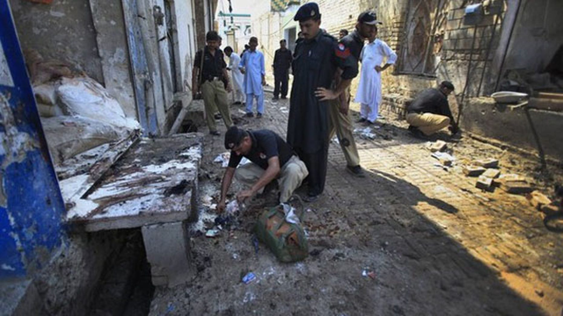 July 26: Policemen collect evidence at the site of a homicide bomb attack in Pabbi town, 26 km (16 miles) east of the provincial capital, Peshawar (Reuters).