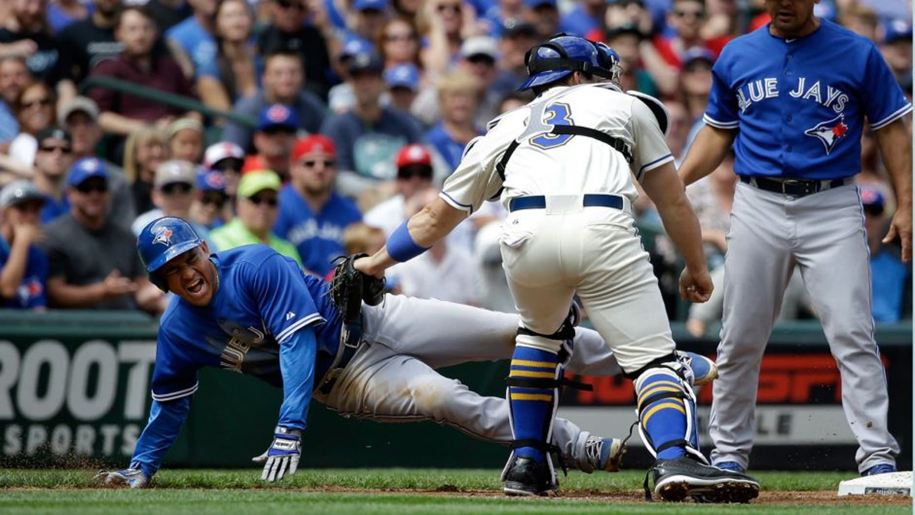 Seattle Mariners catcher Mike Zunino, center, tags Toronto Blue Jays' Ezequiel Carrera, left, out at third base as third base coach Luis Rivera looks on at the end of a triple play in the fourth inning of a baseball game Sunday, July 26, 2015, in Seattle. (AP Photo/Elaine Thompson)