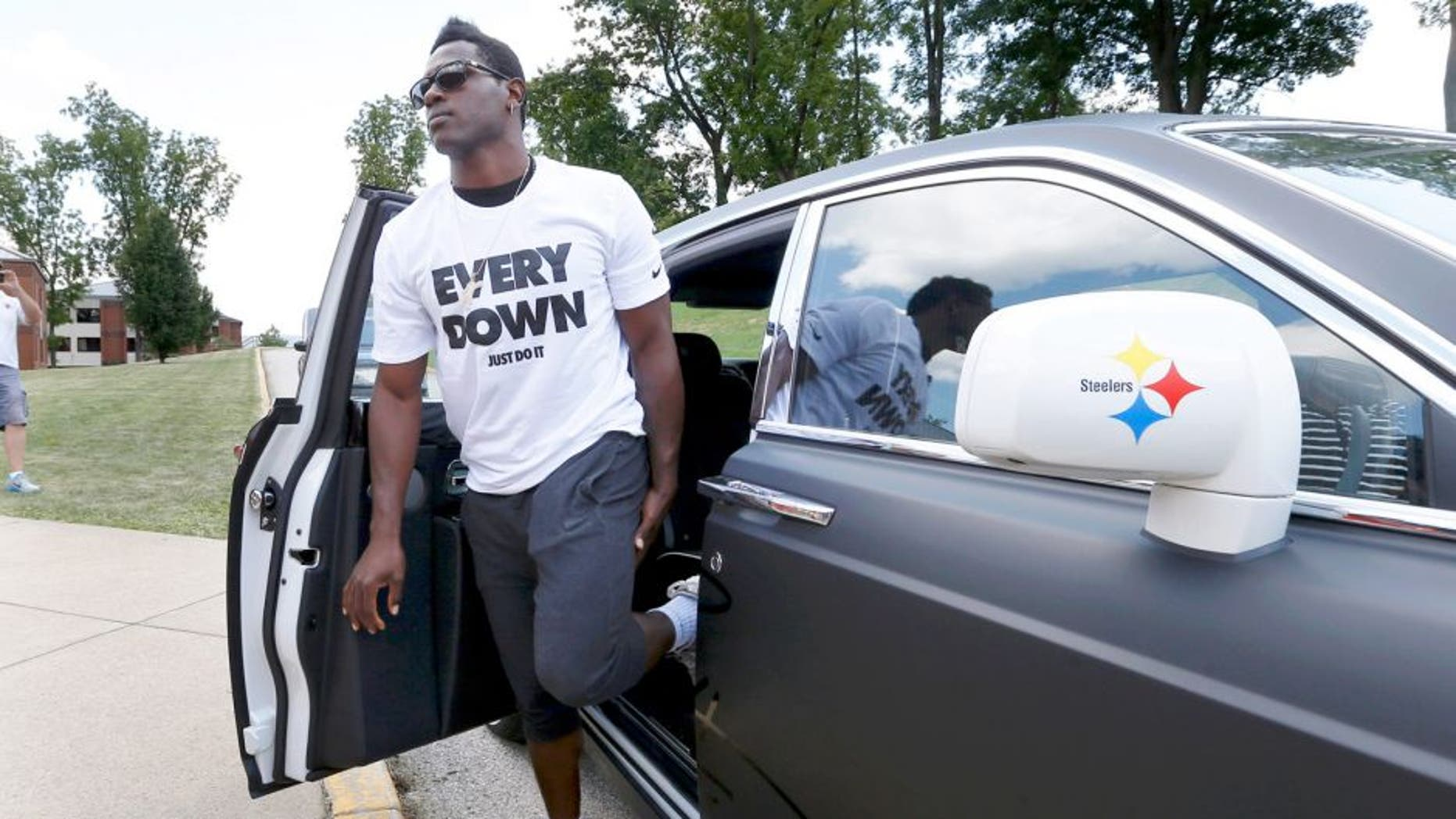 Pittsburgh Steelers wide receiver Antonio Brown gets out of his custom Steelers-themed Rolls Royce as he arrives for NFL football training camp at the team's training facility in Latrobe, Pa., Saturday, July 25, 2015. (AP Photo/Keith Srakocic)