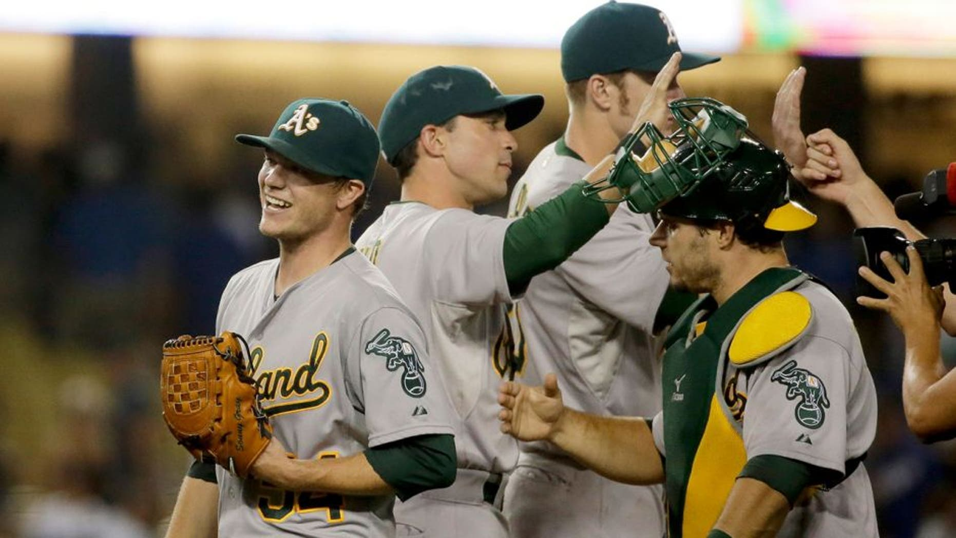 Oakland Athletics starting pitcher Sonny Gray, left, celebrates with teammates after they shutout the Los Angeles Dodgers 2-0 in a baseball game, Tuesday, July 28, 2015, in Los Angeles. (AP Photo/Chris Carlson)