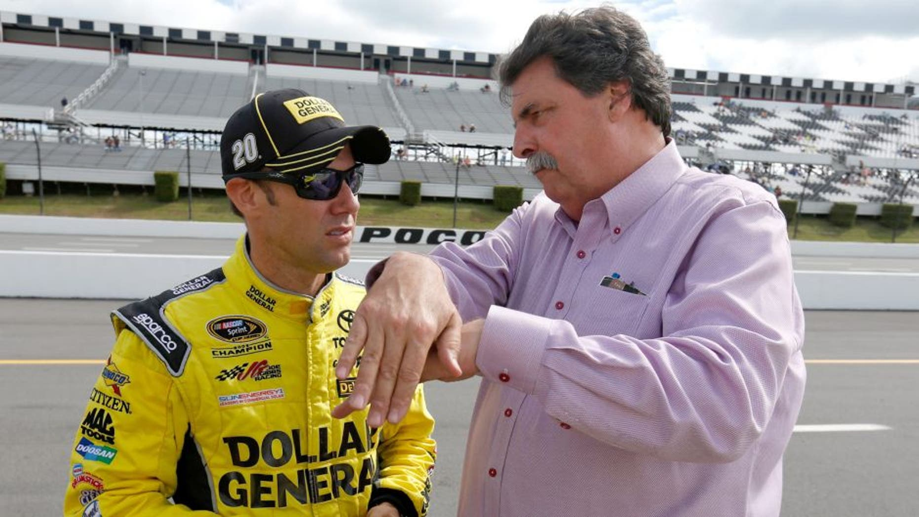 """LONG POND, PA - JUNE 05: Matt Kenseth, driver of the #20 Dollar General Toyota, left, talks with Vice Chairman of NASCAR Mike Helton on the grid prior to qualifying for the NASCAR Sprint Cup Series Axalta """"We Paint Winners"""" 400 at Pocono Raceway on June 5, 2015 in Long Pond, Pennsylvania. (Photo by Todd Warshaw/NASCAR via Getty Images)"""
