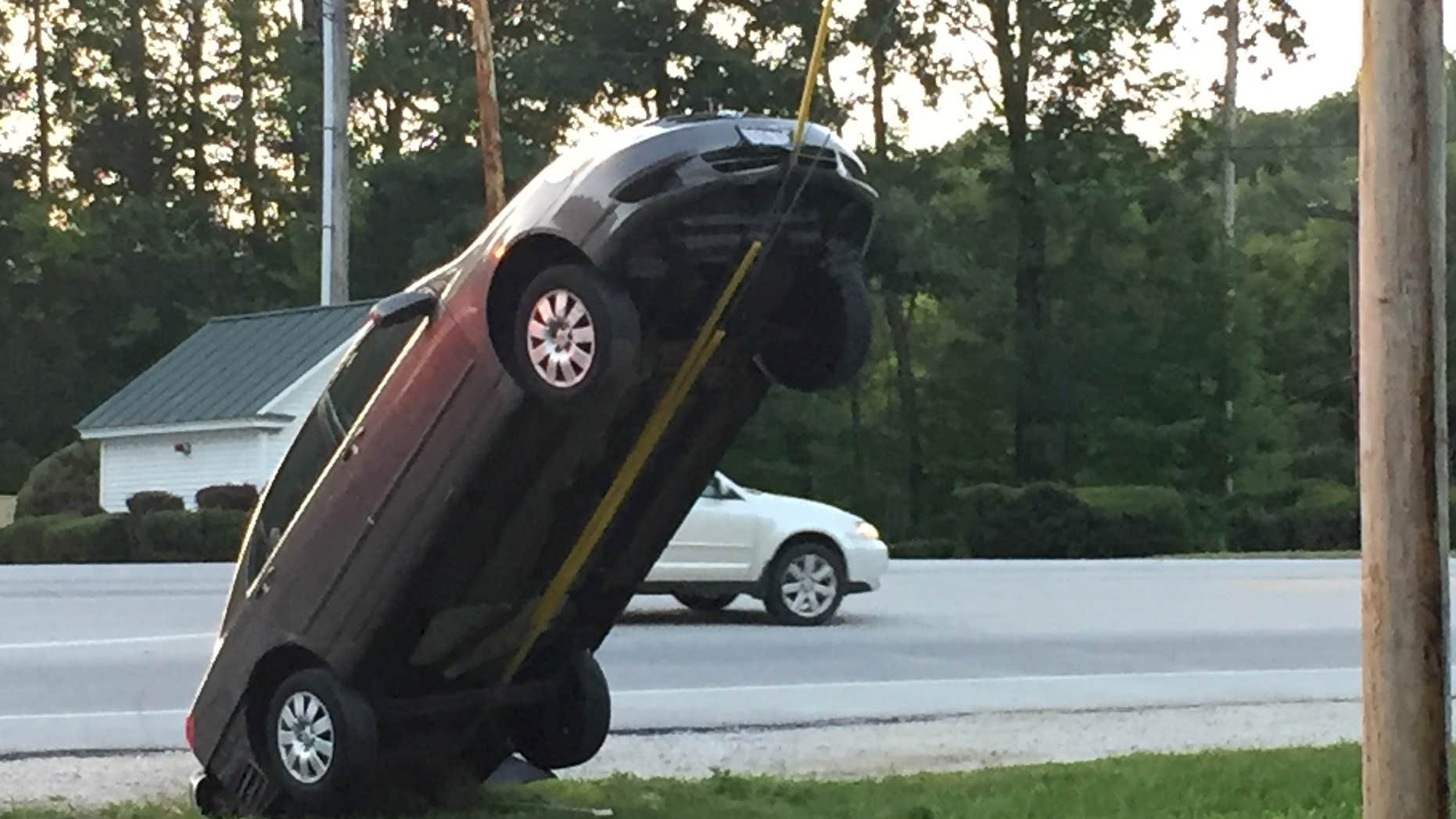 This Wednesday, July 27, 2016, photo provided by G. Ray Ault shows a vehicle on wires attached to a utility pole in Mendon, Vt.
