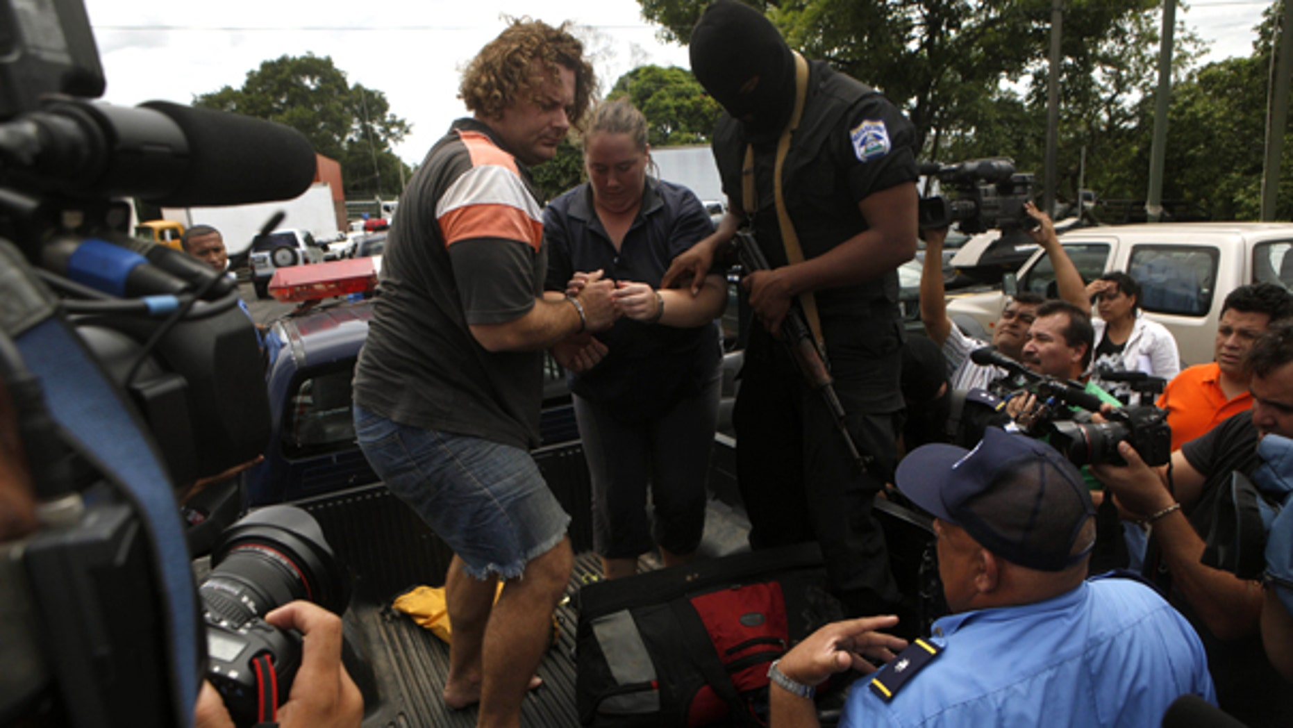 July 29: Detainees identified by Nicaraguan authorities as William Adolfo Cortez and his wife Jane Cortez prepare to walk down a police vehicle before being extradited to Panama from Nicaragua. (AP)