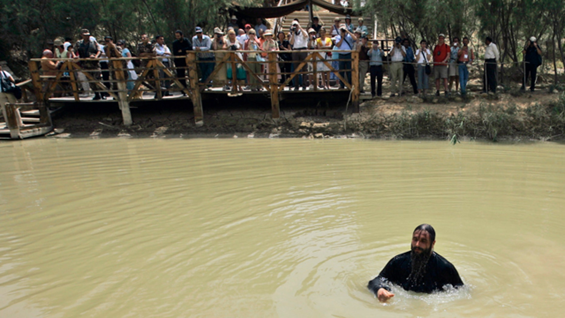 FILE - In this Tuesday, April 22, 2008 file photo, a Christian Greek Orthodox priest bathes in the Jordan River after it was blessed during a baptism ceremony in the waters of the Jordan River at Qasr-el Yahud near Jericho, in the West Bank, during Holy Week. (AP)