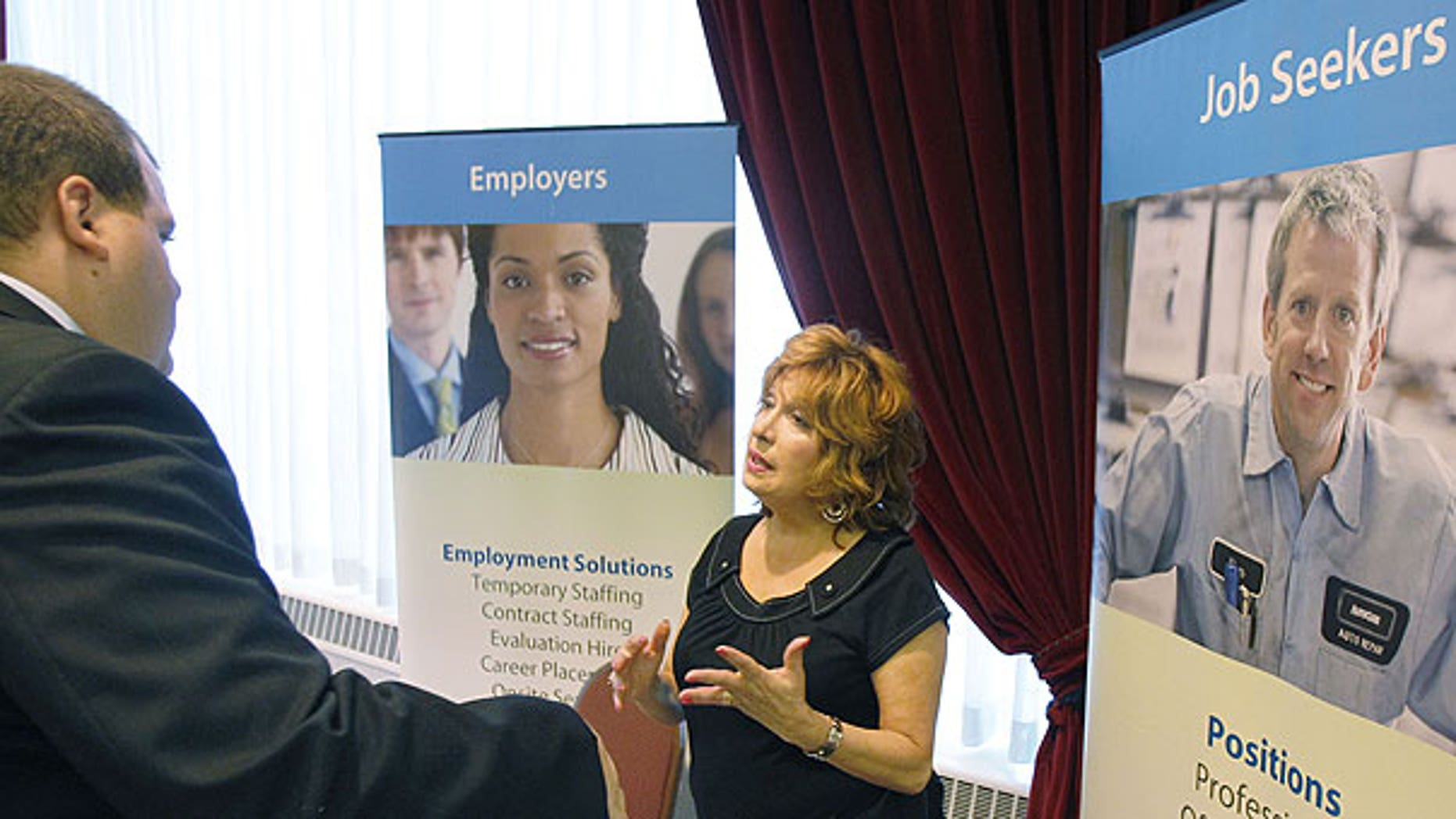 July 21, 2011: Donna Ciora, an employment specialist with Express Employment Professionals, right, talks with people attending the Pittsburgh Career Fair, in Pittsburgh.