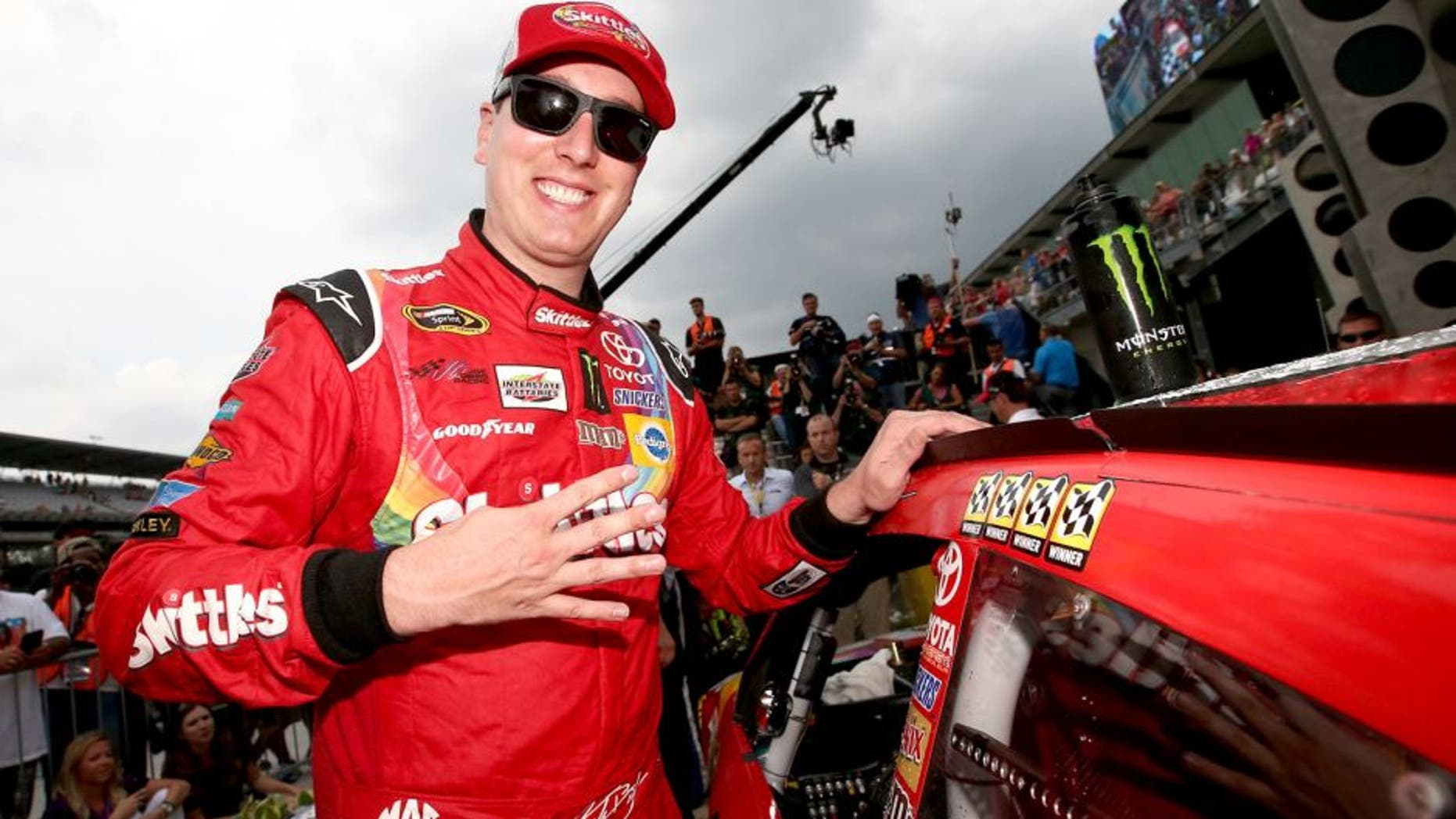 INDIANAPOLIS, IN - JULY 26: Kyle Busch, driver of the #18 Skittles Toyota, places the winner's decal in Victory Lane after winning the NASCAR Sprint Cup Series Crown Royal Presents the Jeff Kyle 400 at the Brickyard at Indianapolis Motor Speedway on July 26, 2015 in Indianapolis, Indiana. (Photo by Sean Gardner/NASCAR via Getty Images)