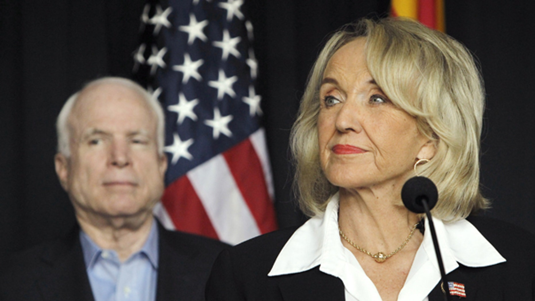 July 30: Gov. Jan Brewer, accompanied by Sen. John McCain pauses before answering a question regarding the latest on the new Arizona immigration law. The two held a news conference to applaud a U.S. Air Force decision to base new F-35 combat jets at Luke Air Force Base in Glendale, a suburb of Phoenix, but the event abruptly ended when the barrage of questions were regarding the immigration law and the next steps the governor was taking in the court battle.