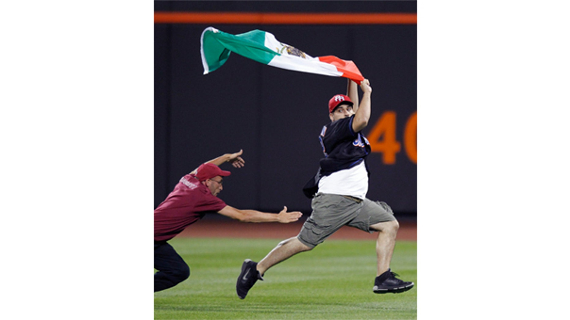 July 30: A Citi Field security guard tries to tackle a young man carrying a Mexican flag who ran onto the field in the seventh inning of the New York Mets vs the Arizona Diamondbacks baseball game in New York.
