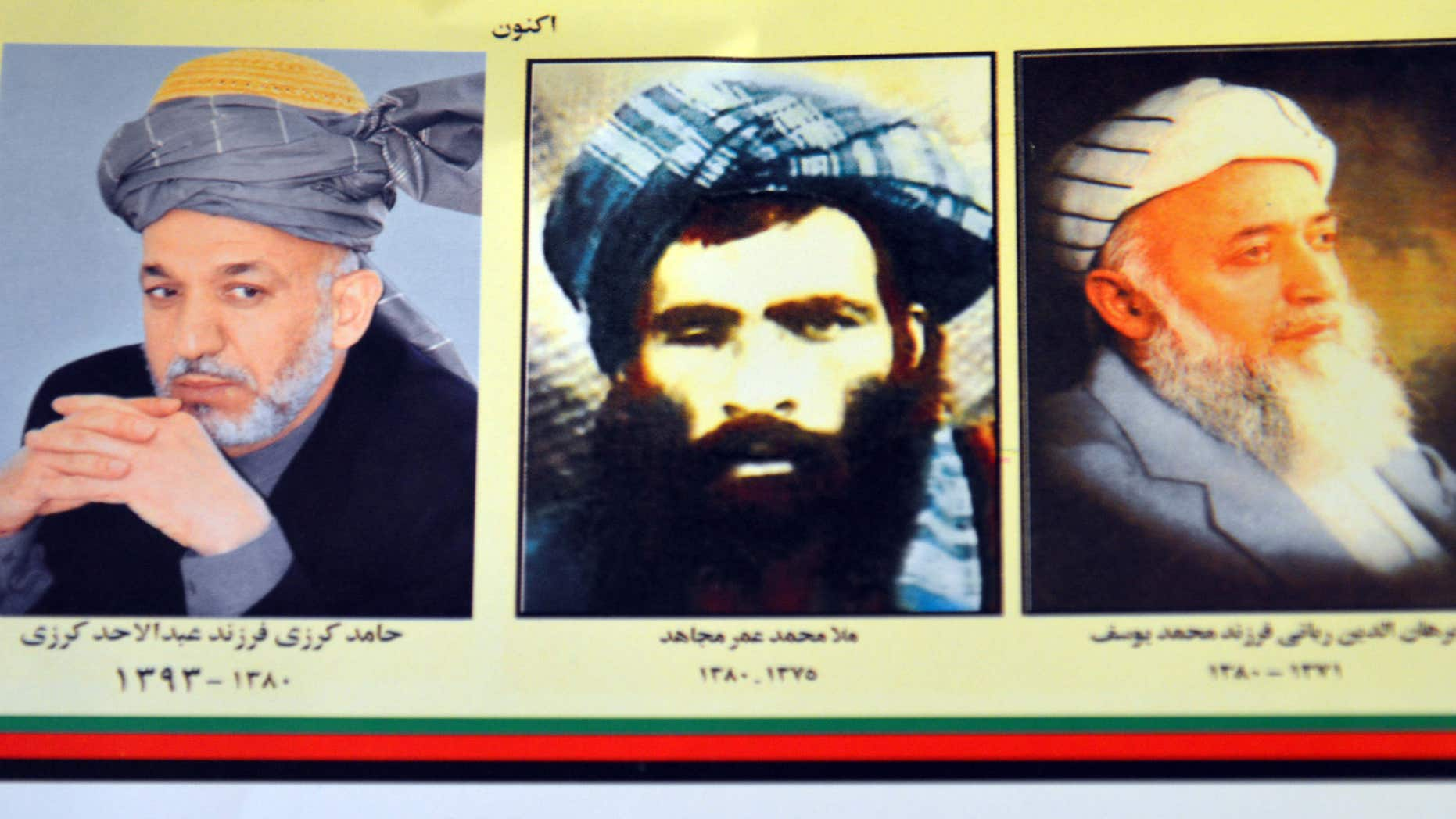 July 30, 2015: An Afghan shop clerk shows a calendar with pictures of Afghan leaders including Mullah Mohammad Omar, center, in Kandahar, south of Kabul, Afghanistan.