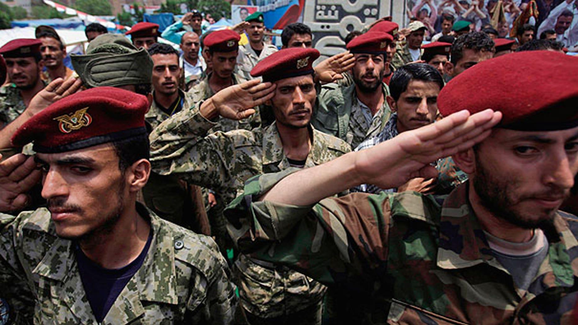July 31: Defected soldiers salute during a protest demanding the resignation of Yemen's President Ali Abdullah Saleh in Sanaa, Yemen.