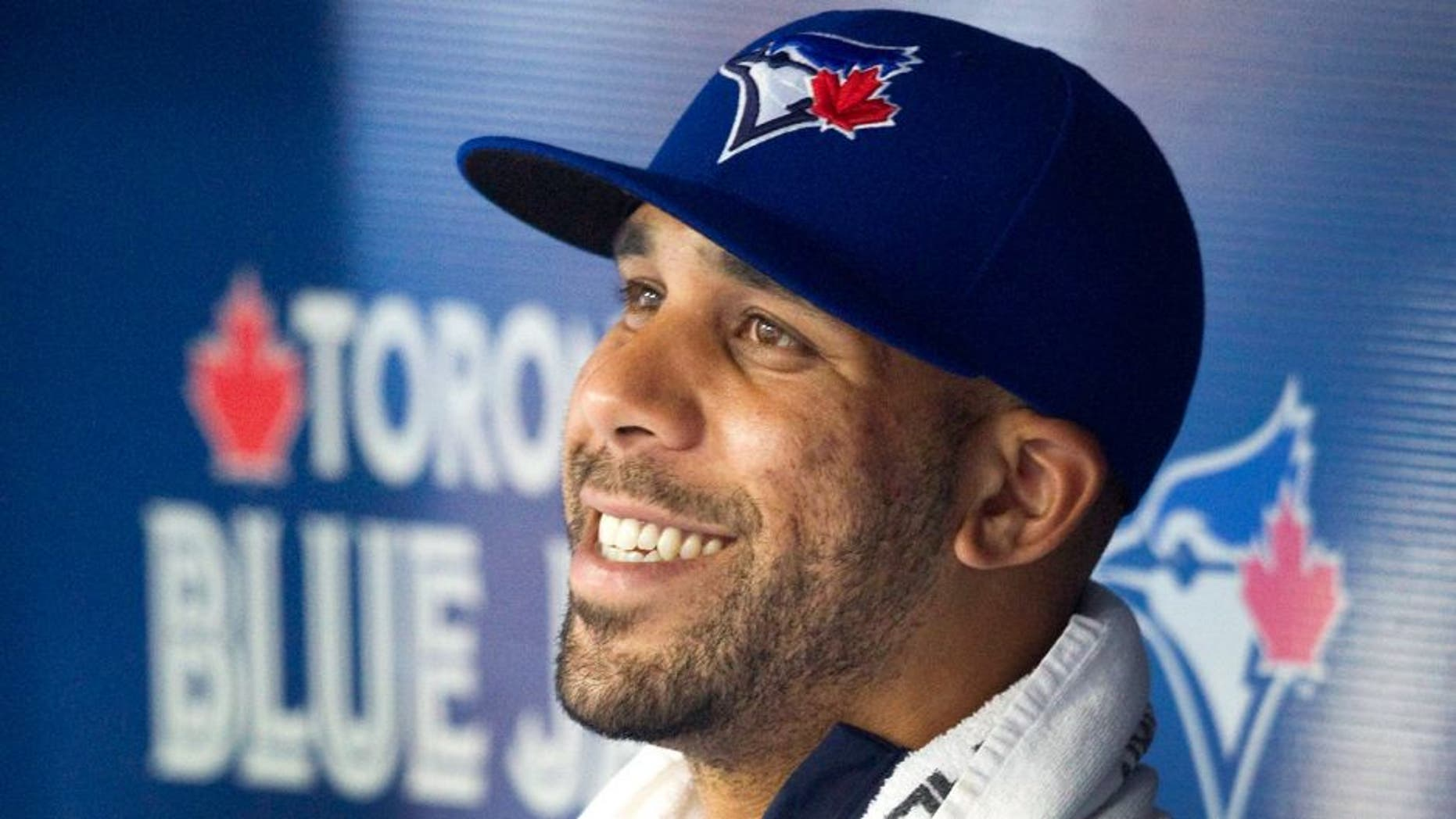 Toronto Blue Jays newly acquired starting pitcher David Price smiles in the dugout as his team plays the Kansas City Royals during the second inning of a baseball game, Friday, July 31, 2015 in Toronto. (Fred Thornhill/The Canadian Press via AP) MANDATORY CREDIT