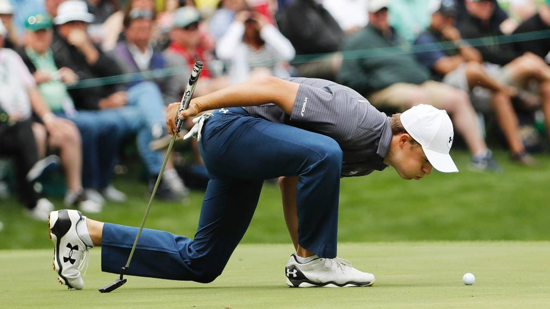 Jordan Spieth blows on his ball on the ninth hole during the par three competition at the Masters golf tournament Wednesday, April 6, 2016, in Augusta, Ga. (AP Photo/David J. Phillip)