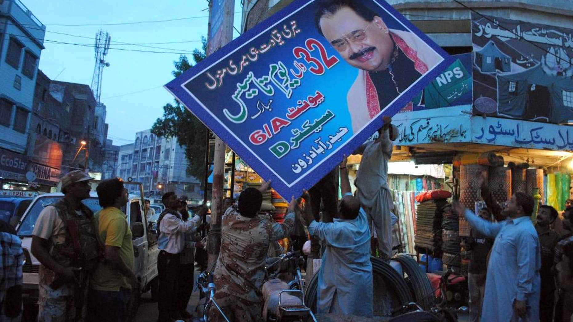FILE - In this Thursday, Aug. 25, 2016 file photo, Pakistani paramilitary forces remove a poster of Altaf Hussain, leader of the Muttahida Qaumi Movement, or MQM, in Hyderabad, Pakistan. Pakistan's Ministry of Interior said it has written a formal request to London to seek legal action against Hussain. A ministry statement says the government sent a dossier on Hussain to U.K. authorities on Tuesday, Aug. 30, 2016, with allegations of inciting violence and disturbing law and order in Pakistan. (AP Photo/Pervez Masih, File)