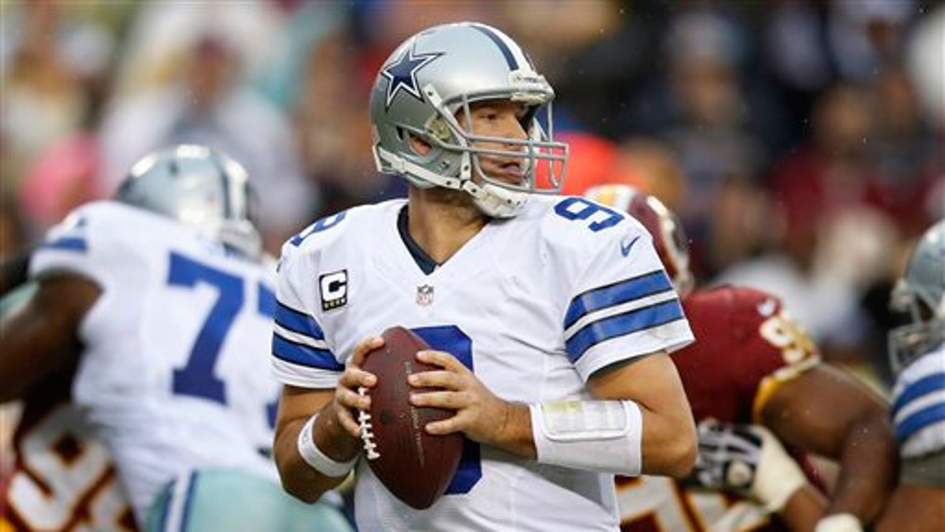 Dallas Cowboys quarterback Tony Romo looks for an opening to pass during the second half of an NFL football game against the Washington Redskins in Landover, Md., Sunday, Dec. 22, 2013. (AP Photo/Evan Vucci)
