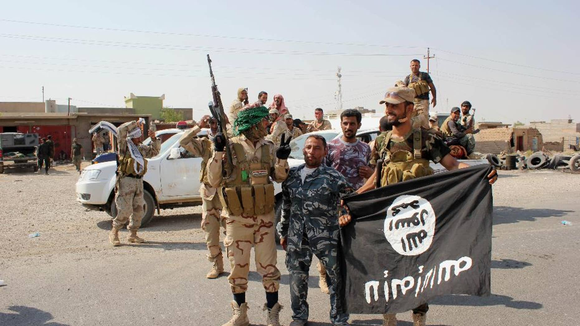 """In this Monday, Sept. 1, 2014 photo, Shiite militiamen hold the flag of the Islamic State group they captured, during an operation outside Amirli, some 105 miles (170 kilometers) north of Baghdad, Iraq. Under the shadow of the Islamic State group threat, governments from France to Indonesia are moving aggressively to block would-be jihadis from taking their fight to Syria and Iraq. New laws make it easier to seize passports. Suspected fighters are being plucked from planes. Authorities are blocking finances and shutting down radical mosques. Behind the scenes, Western intelligence agencies are striving to stay ahead of tech-savvy radicalized Muslims by pressuring Silicon Valley firms to wipe extremist content from websites and toying with new technologies to identify returning fighters at the border. Britain has taken a particularly active role in censoring content deemed to break the country's strict rules against extremist propaganda. U.K. officials recently revealed it had been granted """"super flagger"""" status on sites such as YouTube, meaning their requests to remove videos with grisly content or that encourage terrorism are fast-tracked. (AP Photo)"""