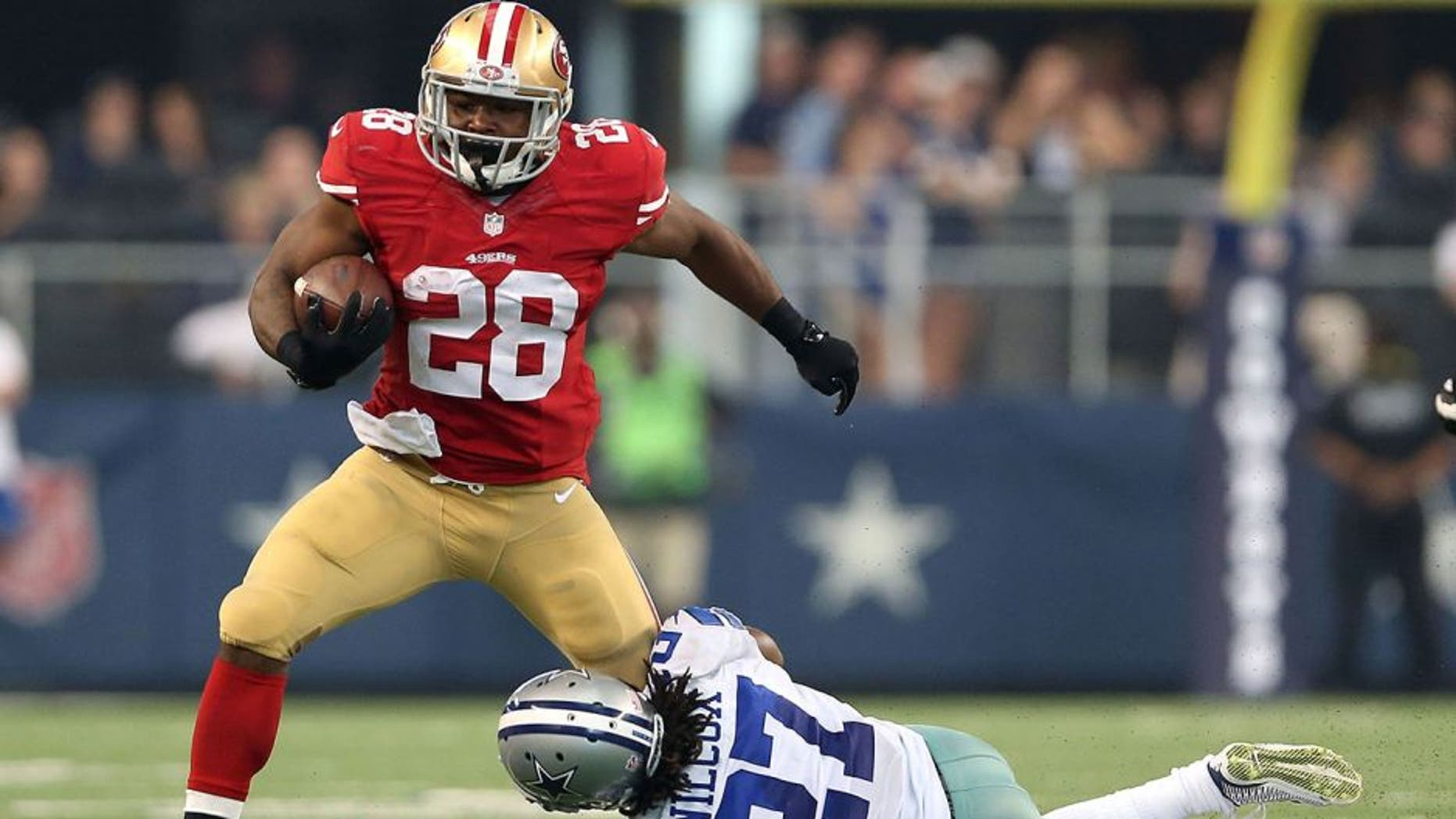 ARLINGTON, TX - SEPTEMBER 07: Carlos Hyde #28 of the San Francisco 49ers tries to break from the grasp of J.J. Wilcox #27 of the Dallas Cowboys in the second half at AT&T Stadium on September 7, 2014 in Arlington, Texas. (Photo by Christian Petersen/Getty Images)