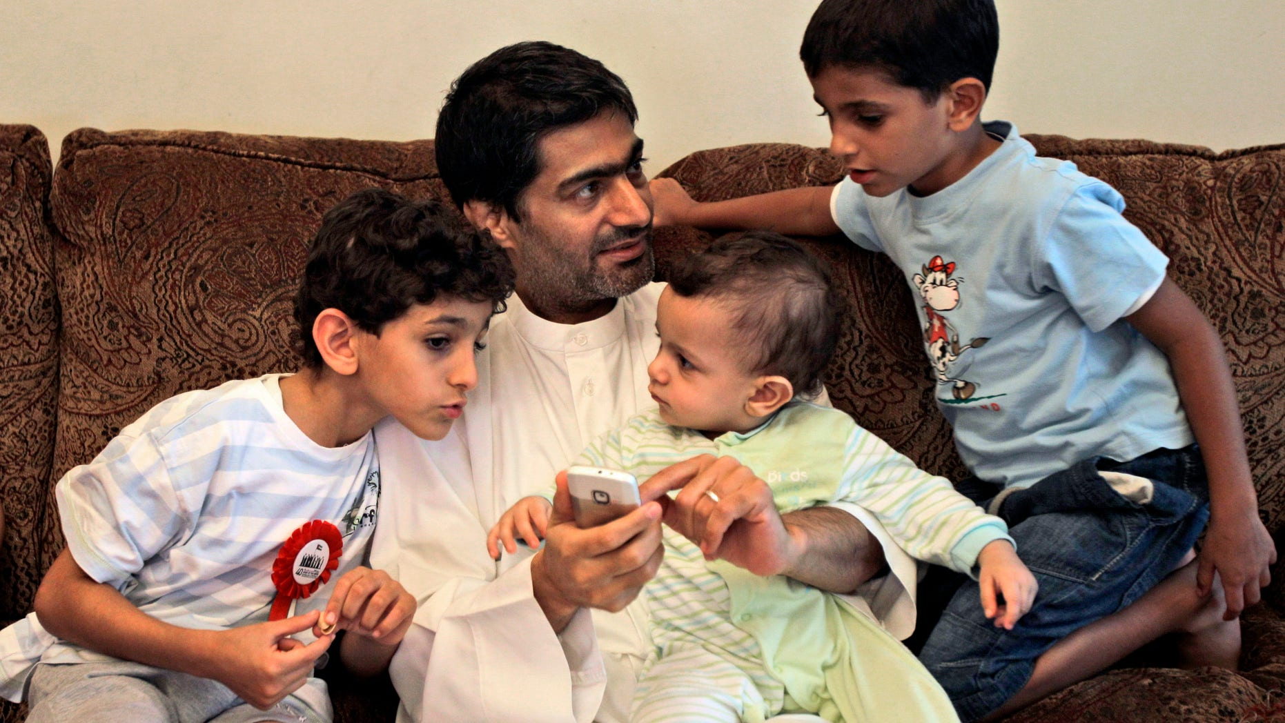 FILE - In this  Tuesday, Nov. 29, 2011 file  photo, Ahmed Mansour, an Emirati blogger and a human rights activists talks with his children after he was pardoned by UAE's president and released from jail in Dubai, United Arab Emirates. In early March 2013, a total of 94 people were put on trial on charges of seeking to overthrow the UAE government and holding ties to the Muslim Brotherhood and other groups. The defendants pleaded not guilty and complained of abuses after their arrests. Mansour and four others including a former legal adviser to the UAE's armed forces were among the first to face arrests for alleged anti-state crimes in early 2011 after signing an online petition urging for political reforms, including free elections for parliament. (AP Photo/Kamran Jebreili, File)