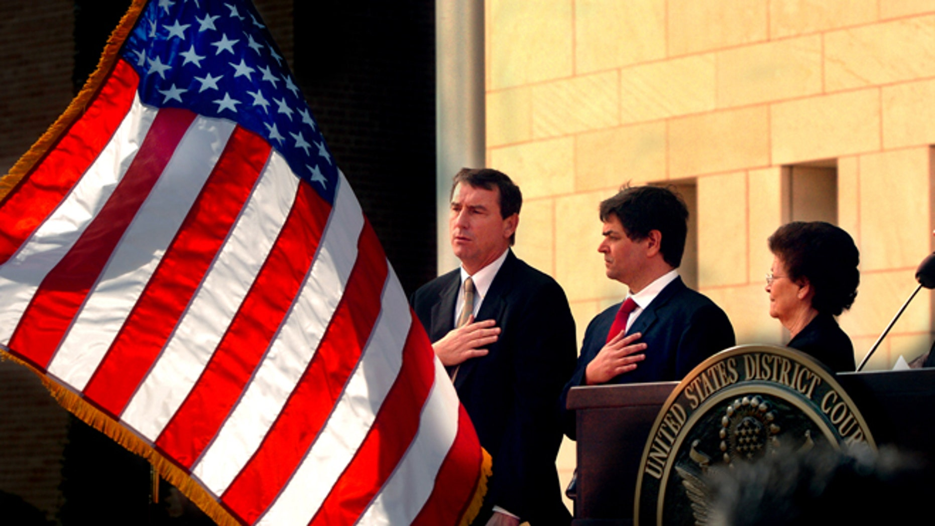 FILE- In this Nov. 14, 2005, file photo, U.S. Southern District Judge Andrew S. Hanen, left, joins with Filemon B. Vela, Jr. and Blanca Vela for the Pledge of Allegiance during the United States Courthouse naming ceremony in Brownsville, Texas. Hanen temporarily blocked President Barack Obama's executive action on immigration Monday, Feb. 16, 2015, giving a coalition of 26 states time to pursue a lawsuit that aims to permanently stop the orders. (AP Photo/The Brownsville Herald, Brad Doherty, File)