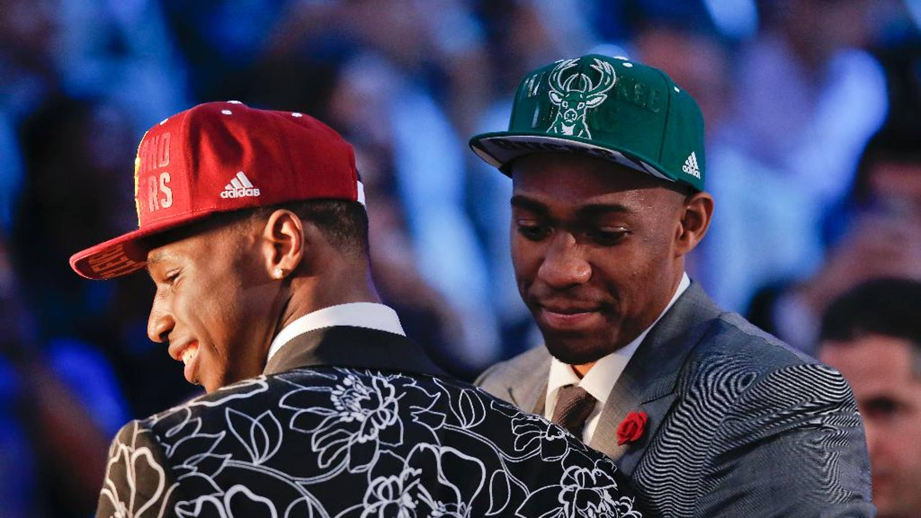 Andrew Wiggins, left, and Jabari Parker stop for television interviews after being selected as the top two picks in the 2014 NBA draft, Thursday, June 26, 2014, in New York. Wiggins was selected number one by the Cleveland Cavaliers and Parker was chosen number two by the Milwaukee Bucks. (AP Photo/Kathy Willens)