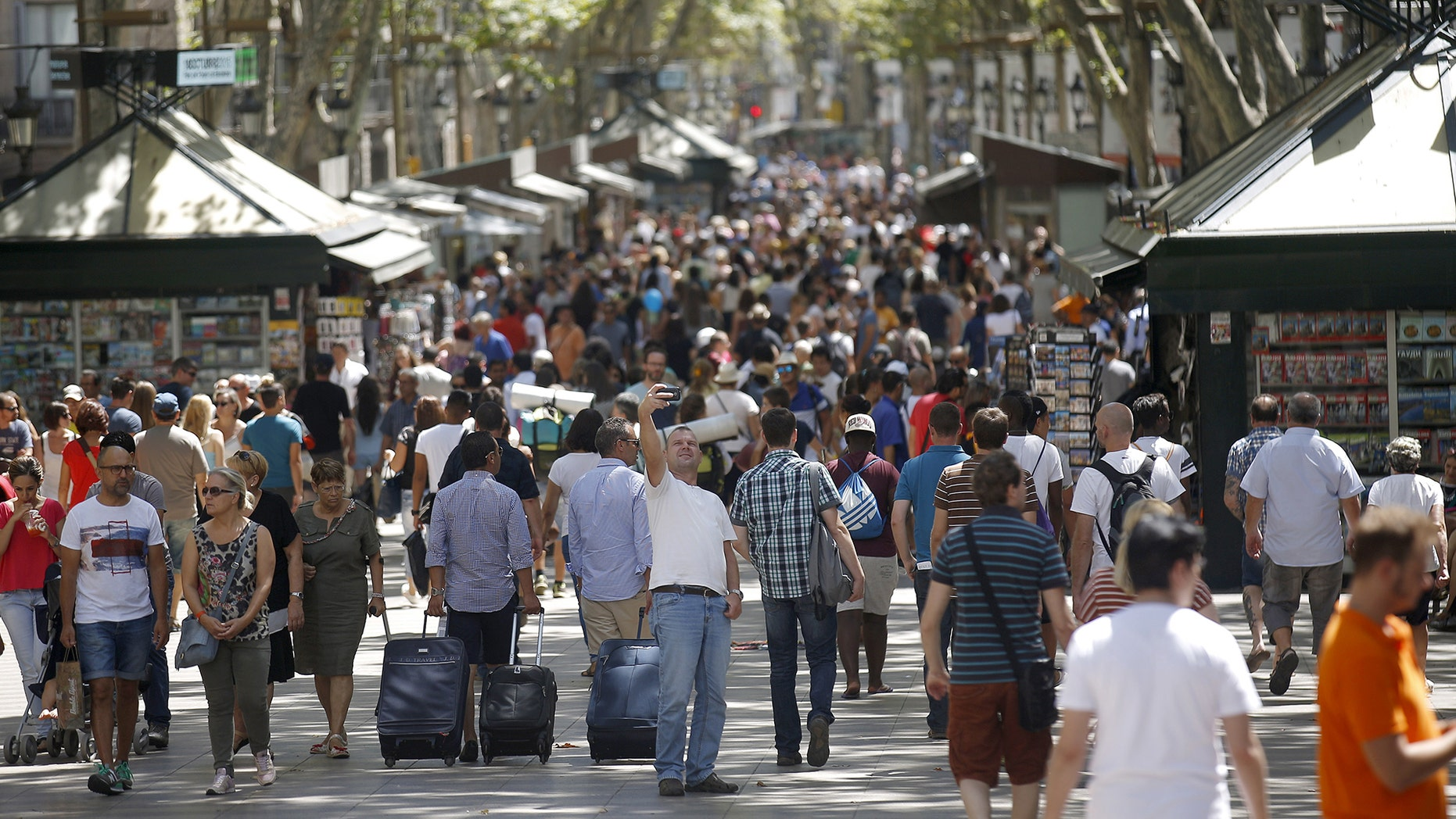 A man takes a selfie at Las Ramblas in Barcelona, Spain, August 16, 2015. Barcelona's new mayor is picking a fight with home rental websites as she tries to crack down on uncontrolled tourism that she fears could drive out poor residents and spoil the Catalan capital's charm. Picture taken on August 16, 2015. REUTERS/Albert Gea - RTX1PQRT
