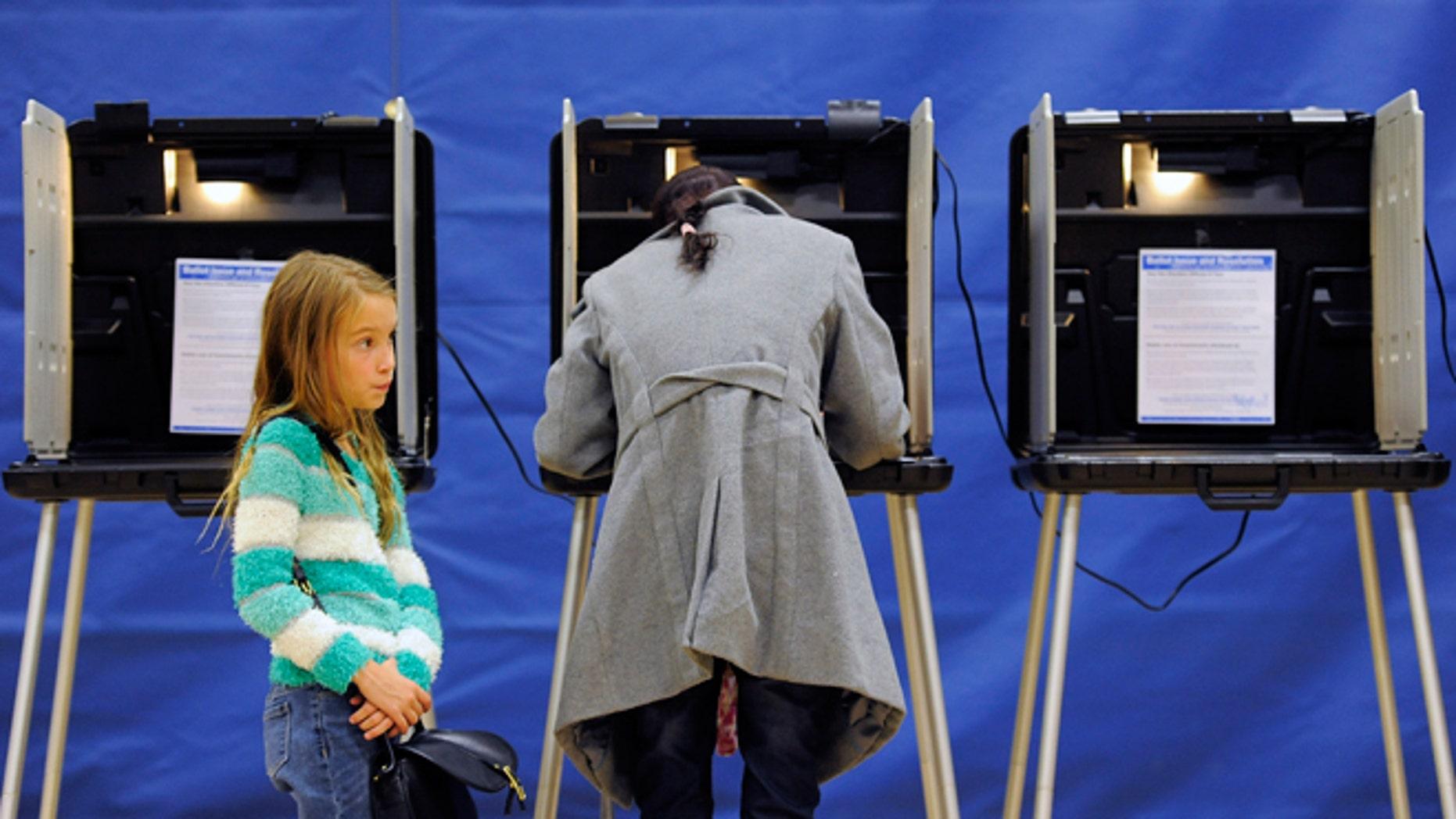 Nov. 4, 2014: Alice Kunde, 8, left, waits for her mother Laura Kunde to vote at the Barnum Recreation Center in Denver.