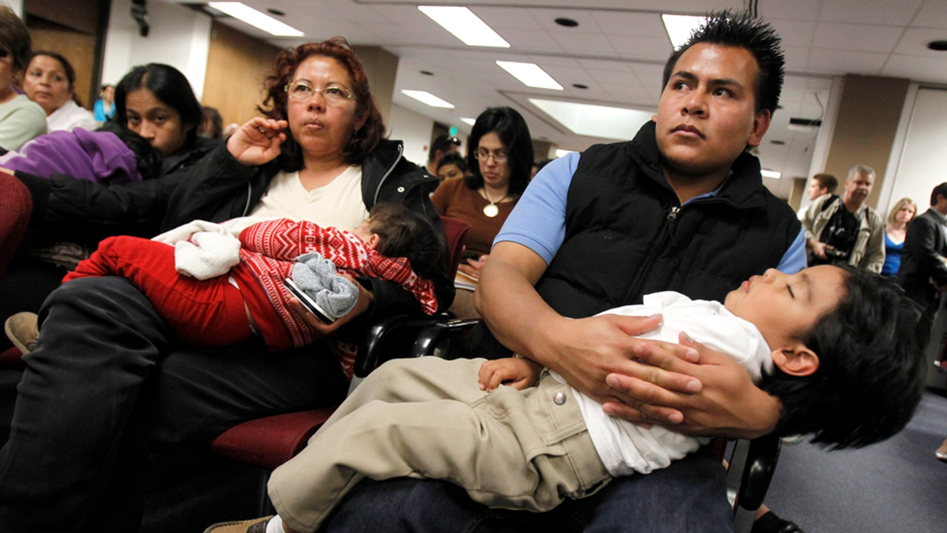"""Marko Garduno, top right, holds a sleeping Dillon Garduno, 2 1/2, as they join dozens of others as they listen to Arizona lawmakers give their first hearing to a bill that challenges automatic U.S. citizenship for children of illegal immigrants, the state's latest foray into the national debate over illegal immigration at the Arizona Capitol, Monday, Feb. 7, 2011, in Phoenix.  The bill to be heard Monday by the Senate judiciary committee seeks a court interpretation on an element of the 14th Amendment, which guarantees citizenship to people born in the U.S. who are """"subject to the jurisdiction"""" of this country. (AP Photo/Ross D. Franklin)"""