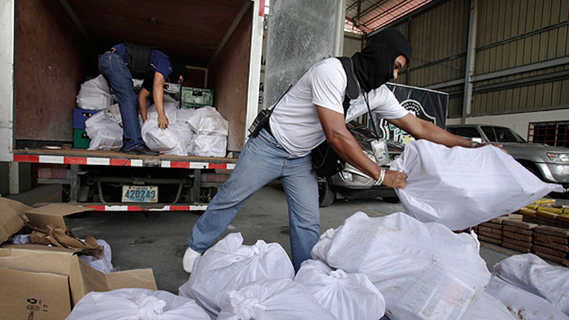 Aug. 1: Anti-narcotic agents unload sacks containing packages of heroin during a press conference in Panama City.