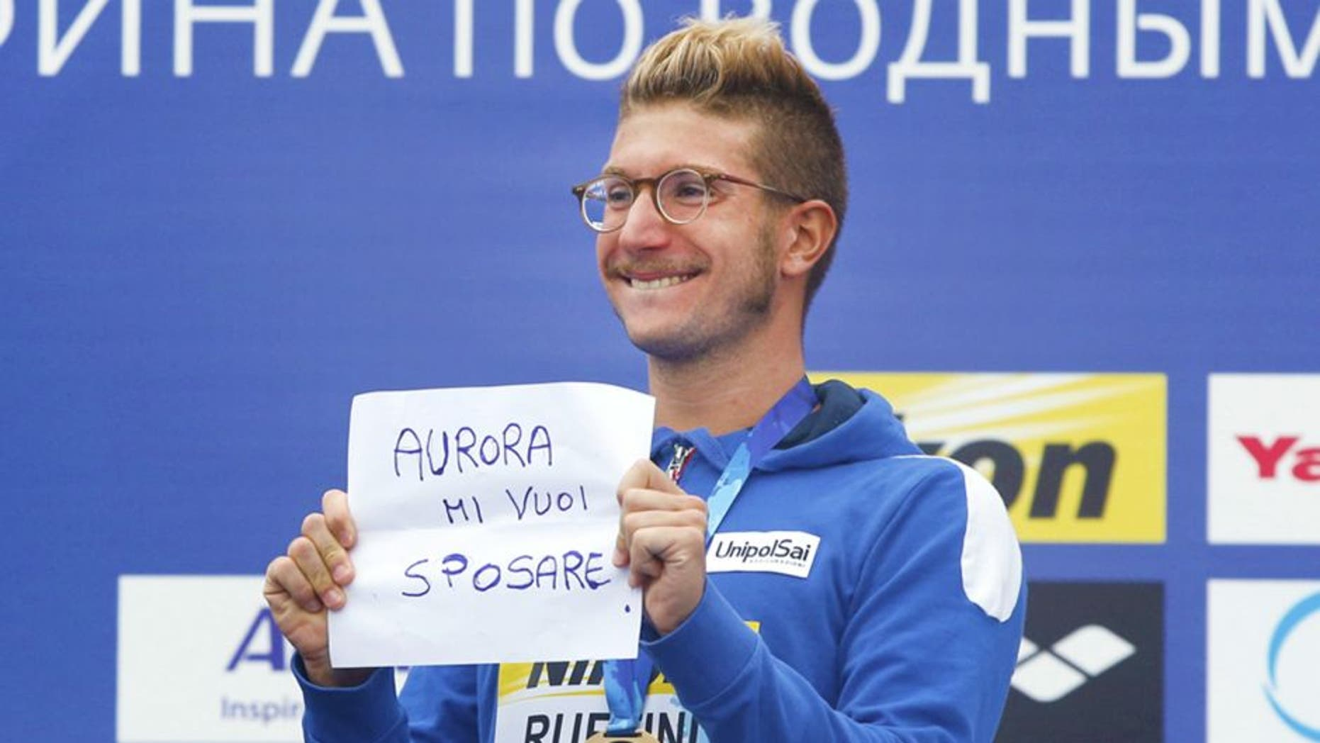 "Italy's gold medal winner Simone Ruffini shows a placard ""Aurora, you want to marry me"" during the ceremony for the men's 25km open water swim competition at the Swimming World Championships in Kazan, Russia, Saturday, Aug. 1, 2015. (AP Photo/Sergei Grits)"