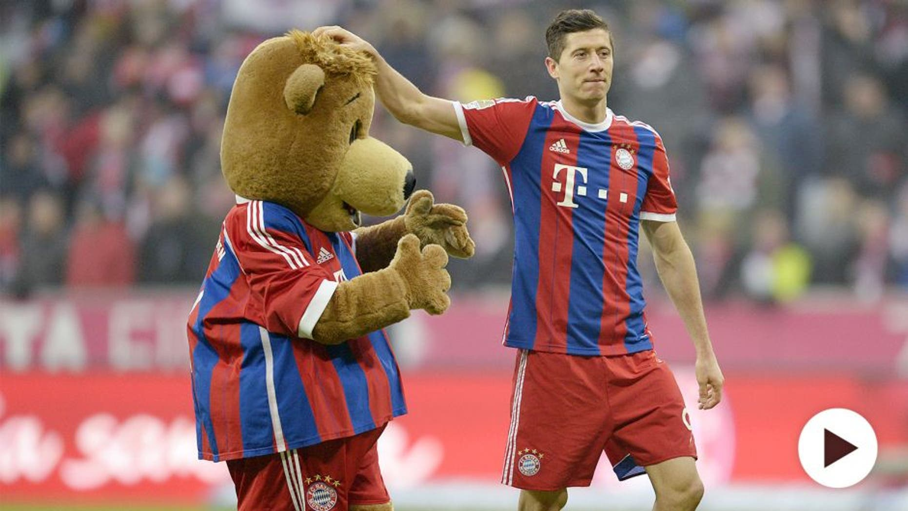 Bayern Munich's Polish striker Robert Lewandowski plays with the maskot after the German first division Bundesliga football match FC Bayern Munich vs Hamburger SV at the Allianz Arena in Munich, southern Germany, on February 14, 2015. AFP PHOTO / CHRISTOF STACHE RESTRICTIONS - DFL RULES TO LIMIT THE ONLINE USAGE DURING MATCH TIME TO 15 PICTURES PER MATCH. FOR FURTHER QUERIES PLEASE CONTACT DFL DIRECTLY AT + 49 69 650050 (Photo credit should read CHRISTOF STACHE/AFP/Getty Images)