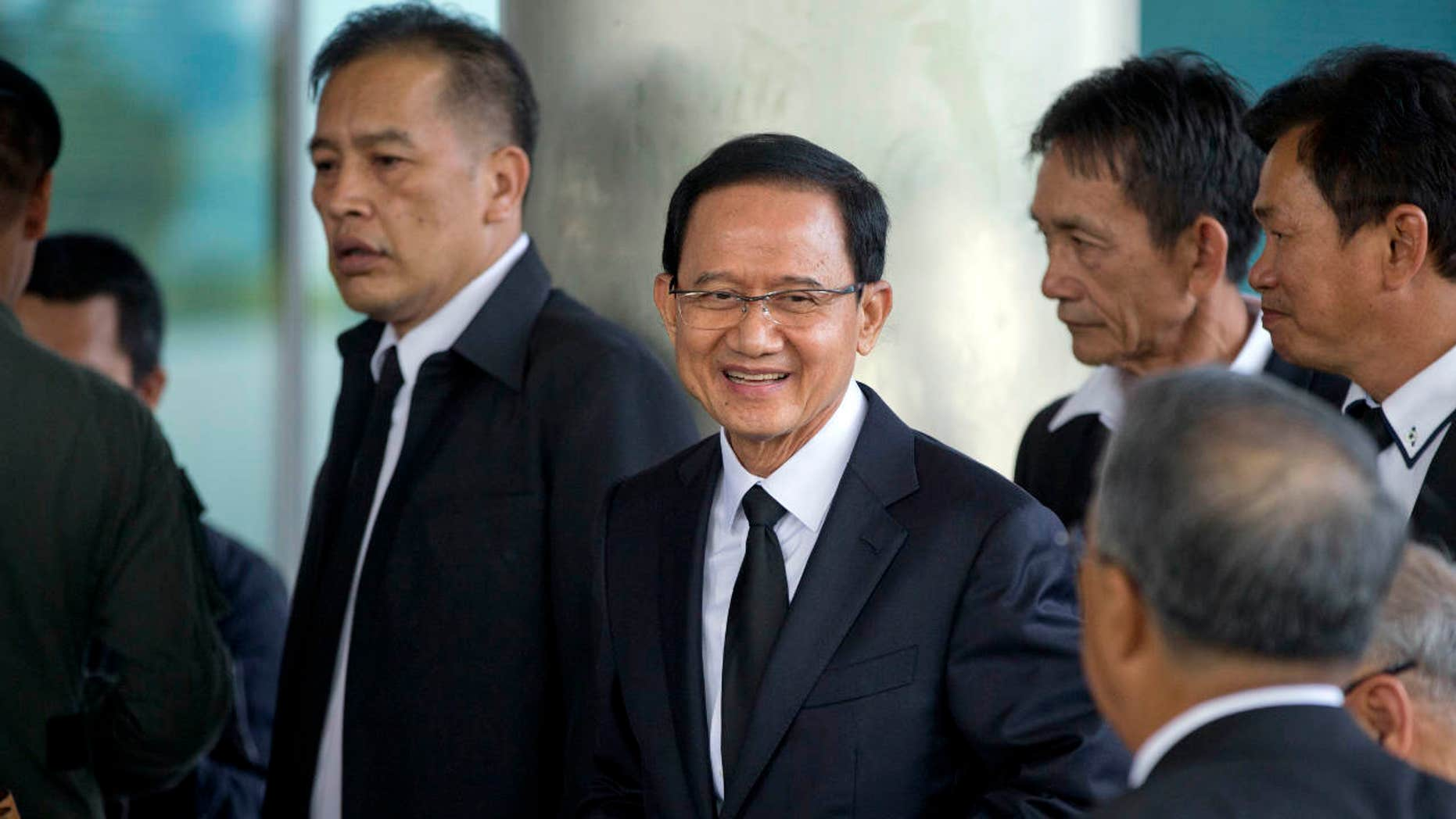 Thailand's former Prime Minister Somchai Wongsawat, center, smilies upon his arrival at a courthouse Wednesday, Aug. 2, 2017, in Bangkok, Thailand.