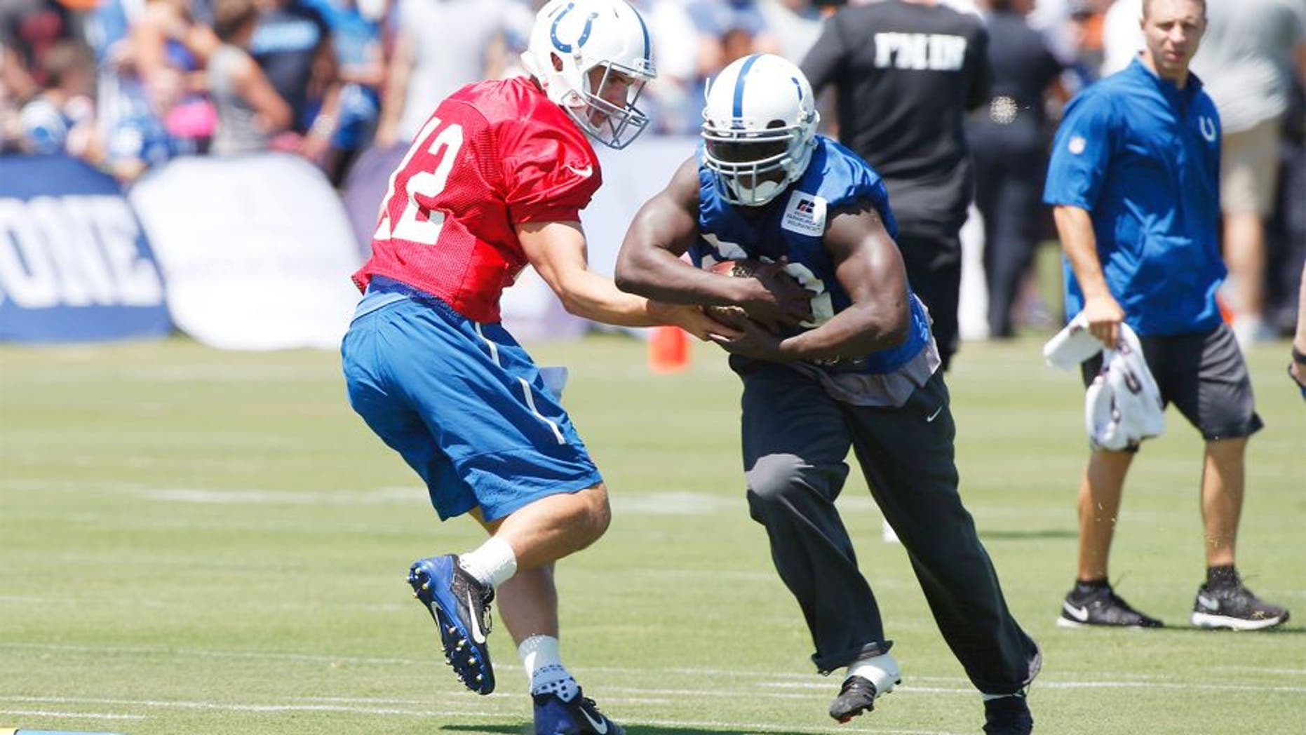 Aug 2, 2015; Anderson, IN, USA; Indianapolis Colts quarterback Andrew Luck (12) hands the ball off to running back Frank Gore (23) during training camp at Anderson University. Mandatory Credit: Brian Spurlock-USA TODAY Sports