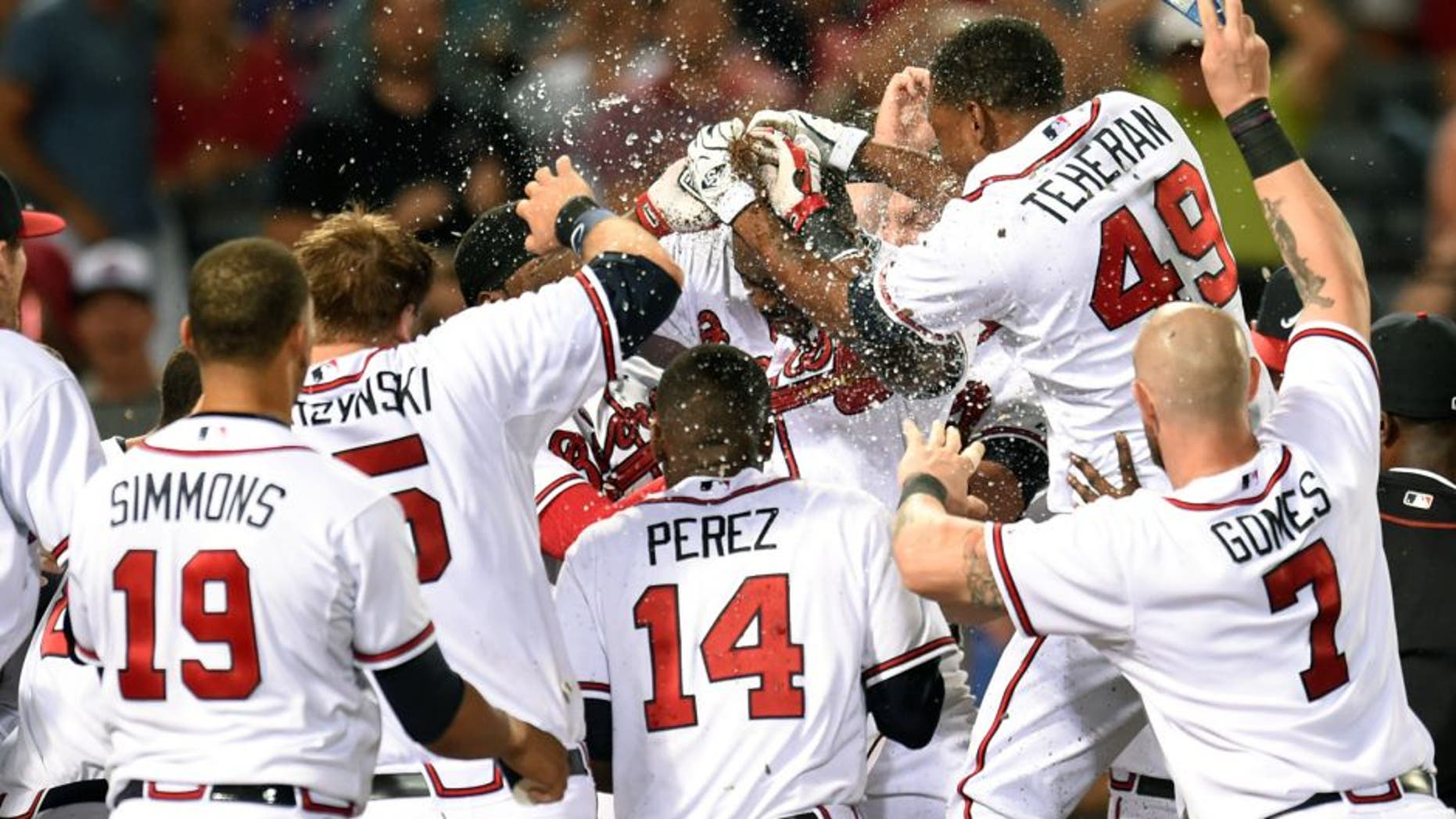 Aug 3, 2015; Atlanta, GA, USA; Atlanta Braves third baseman Adonis Garcia (center) is mobbed by teammates after hitting a game winning two run home run against the San Francisco Giants during the twelfth inning at Turner Field. The Braves defeated the Giants 9-8 in 12 innings. Mandatory Credit: Dale Zanine-USA TODAY Sports
