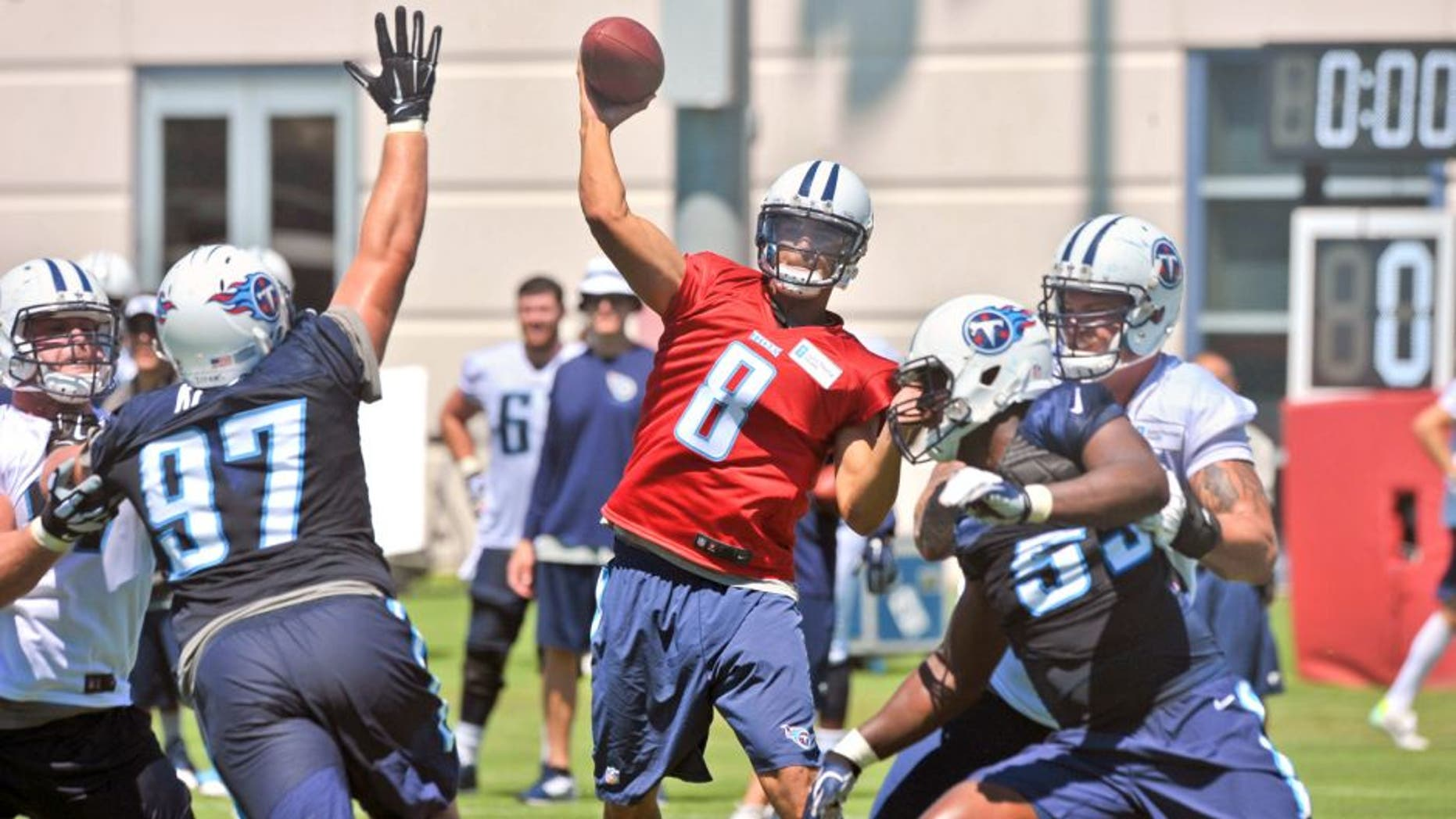 Jul 31, 2015; Nashville, TN, USA; Tennessee Titans quarterback Marcus Mariota (8) passes against Titans defensive lineman Karl Klug (97) during his first day of training camp at Saint Thomas Sports Park. Mandatory Credit: Jim Brown-USA TODAY Sports