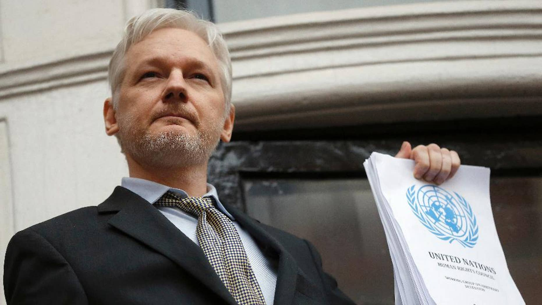 FILE - This is a Friday, Feb. 5, 2016 file photo of WikiLeaks founder Julian Assange holds a U.N. report as he speaks on the balcony of the Ecuadorian Embassy in London.  A U.N. panel is sticking by its opinion that WikiLeaks founder Julian Assange is a victim of arbitrary detention, rejecting a request by Britain to review the case. The Working Group on Arbitrary Detention found that Britain had not presented enough new information to merit a new examination. The panel made the decision at a meeting last week, the U.N. human rights office said Wednesday, Nov. 30, 2016. (AP Photo/Frank Augstein, File)