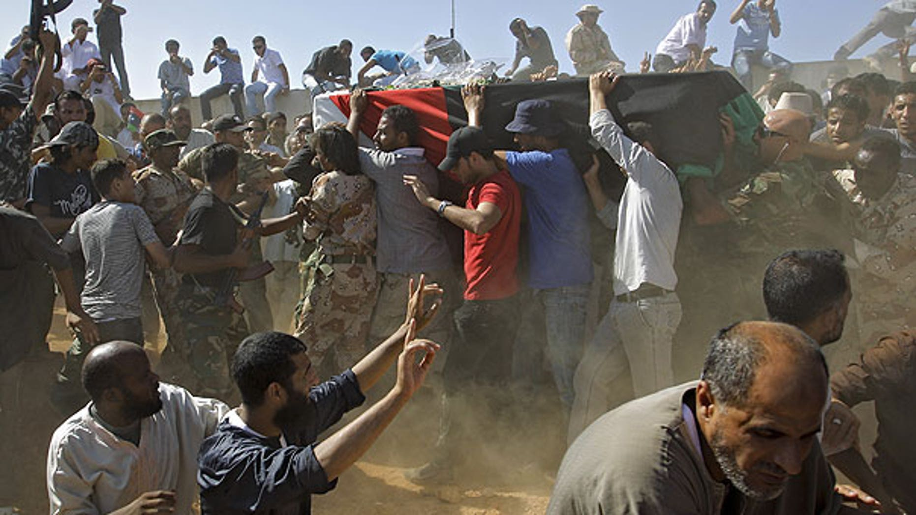 July 29: Libyan men carry a coffin, gesture and chant slogans during funeral of Libyan rebels' military chief Abdel-Fattah Younis in the rebel-held town of Benghazi, Libya.