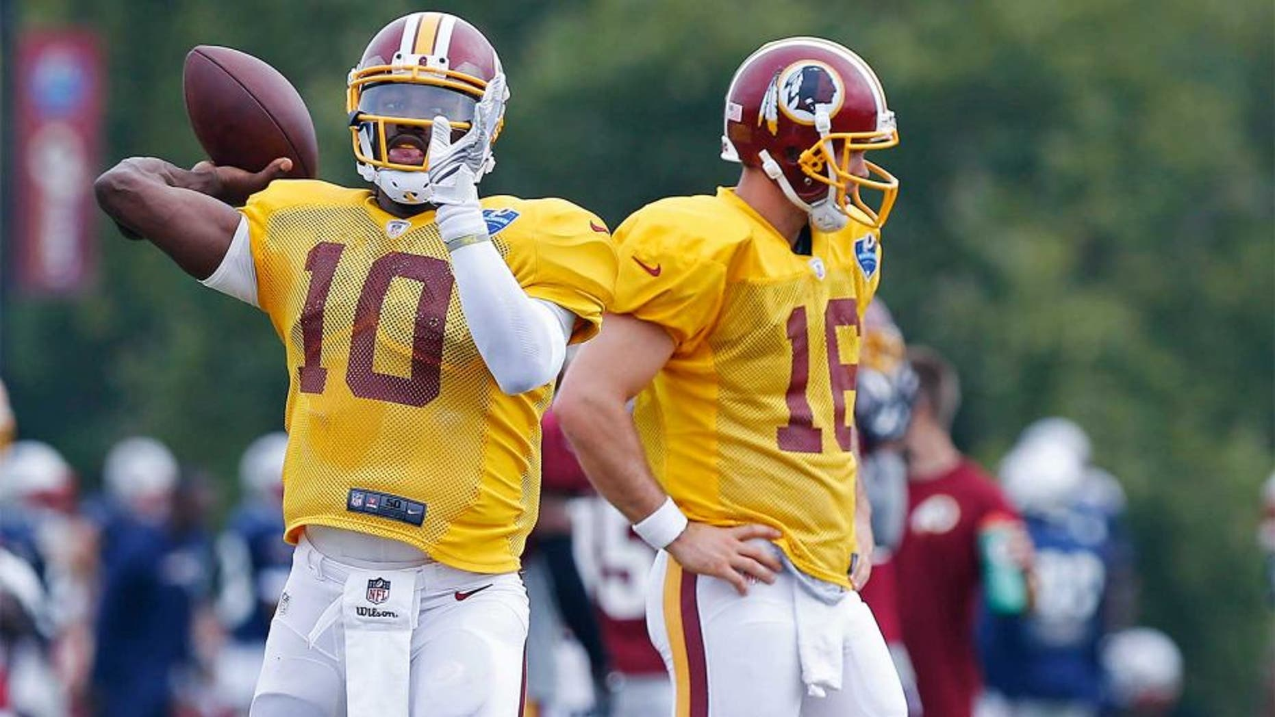 Aug 4, 2014; Richmond, VA, USA; Washington Redskins quarterback Robert Griffin III (10) throws the ball as Redskins quarterback Colt McCoy (16) looks on during joint practice with the New England Patriots on day ten of training camp at the Bon Secours Washington Redskins Training Center. Mandatory Credit: Geoff Burke-USA TODAY Sports