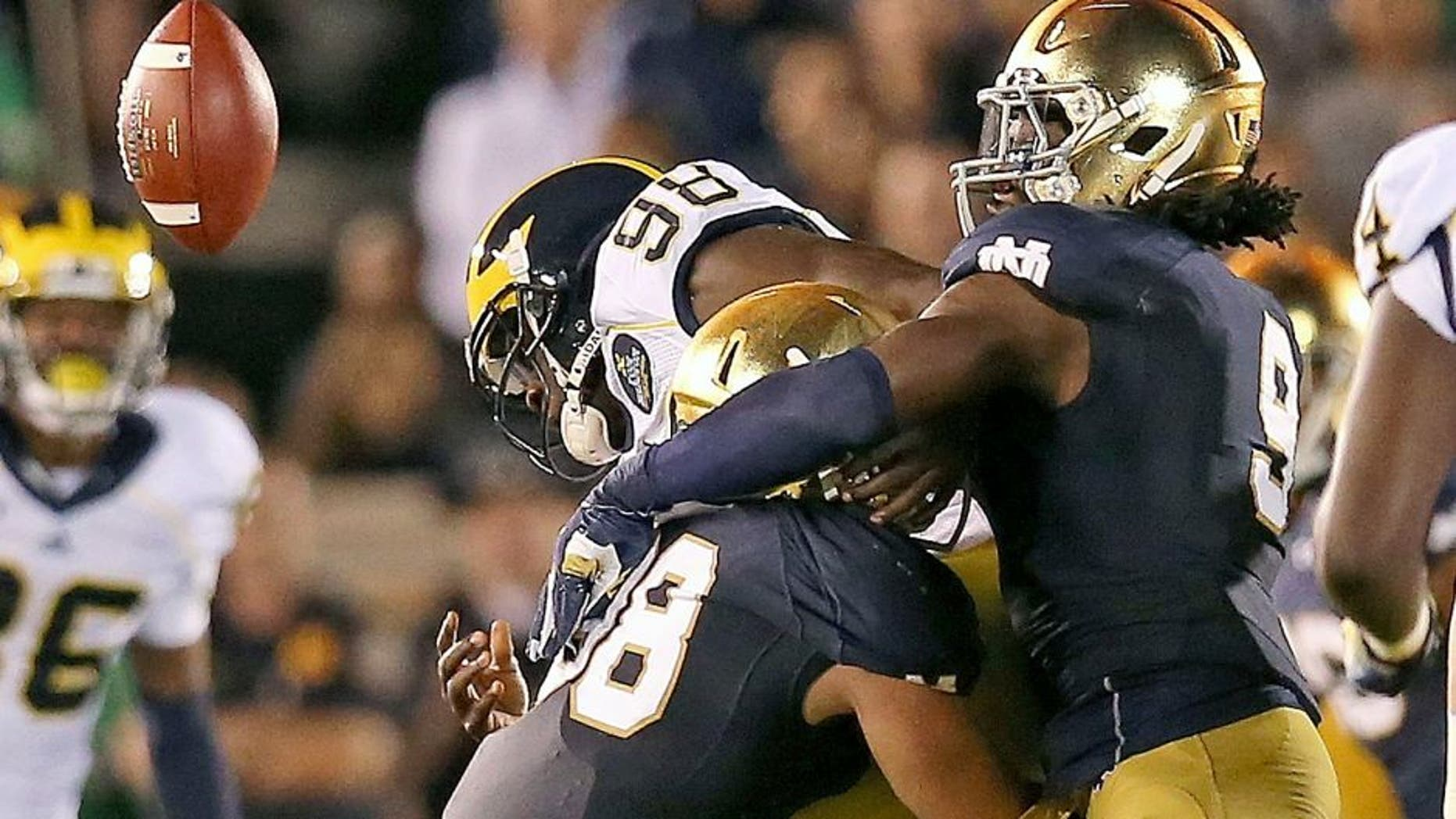 SOUTH BEND, IN - SEPTEMBER 06: Devin Gardner #98 of the Michigan Wolverines fumbles the ball as he is hit by Joe Schmidt #38 (L) abd Jaylon Smith #9 of the Notre Dame Fighting Irish at Notre Dame Stadium on September 6, 2014 in South Bend, Indiana. (Photo by Jonathan Daniel/Getty Images)