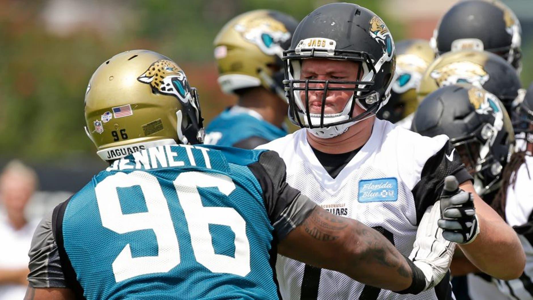 Jacksonville Jaguars tackle Josh Wells (72) blocks defensive tackle Michael Bennett (96) during a light scrimmage at NFL football training camp, Friday, July 31, 2015, in Jacksonville, Fla. (AP Photo/John Raoux)