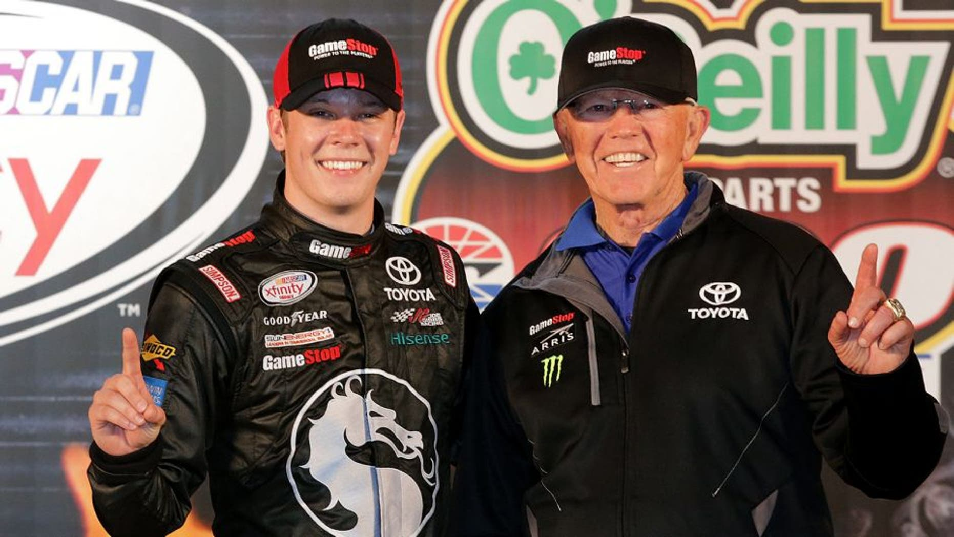 FORT WORTH, TX - APRIL 10: Erik Jones, driver of the #20 GameStop/Mortal Kombat X Toyota, and team owner Joe Gibbs pose with the trophy in Victory Lane after winning the NASCAR XFINITY Series O'Reilly Auto Parts 300 at Texas Motor Speedway on April 10, 2015 in Fort Worth, Texas. (Photo by Jerry Markland/Getty Images for Texas Motor Speedway)