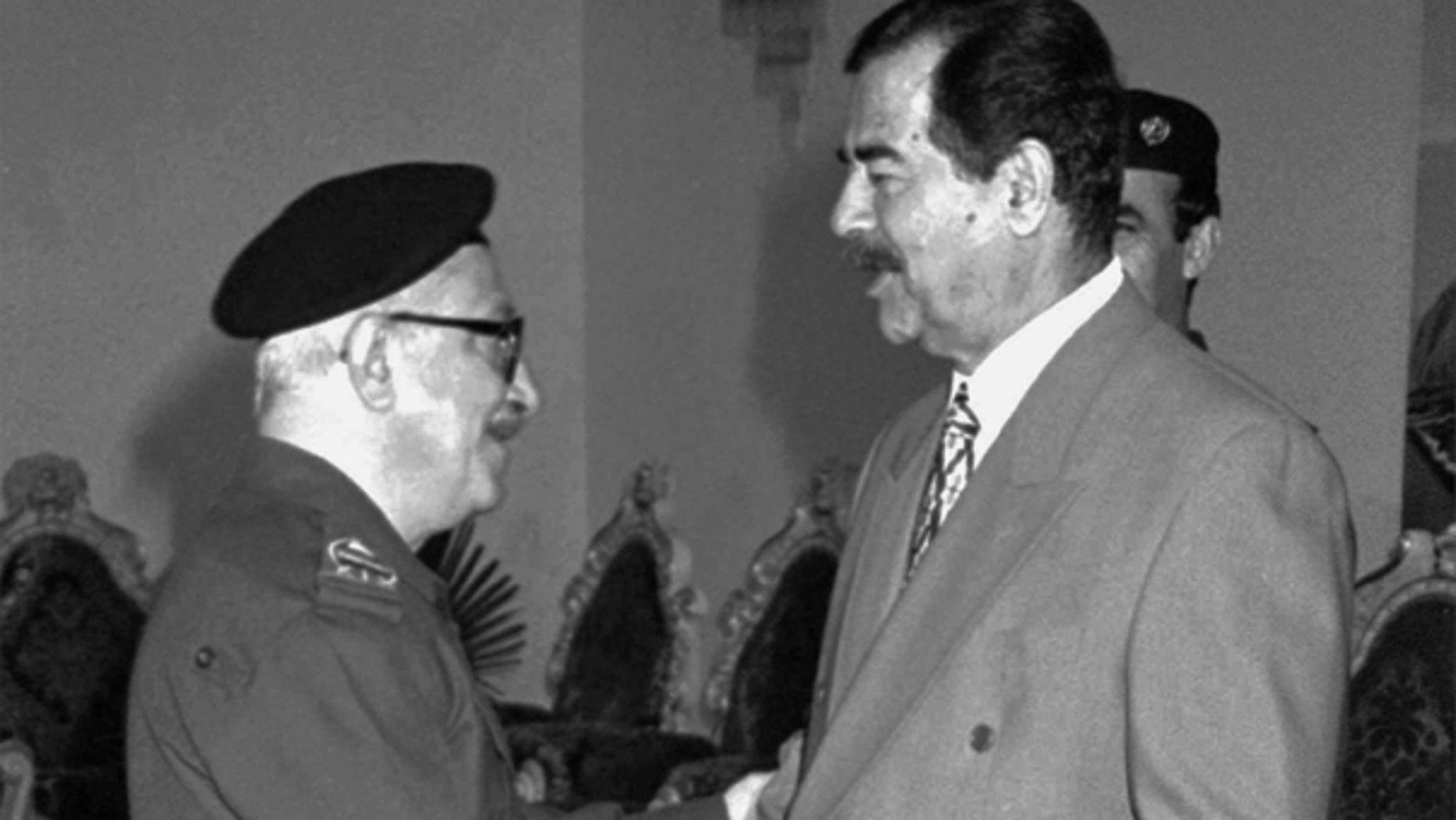 In this Jan. 29, 1998 file photo, Iraqi Deputy Premier Tariq Aziz, left, greets President Saddam Hussein on Eid al-Fitr, the end of Ramadan in Baghdad, Iraq.